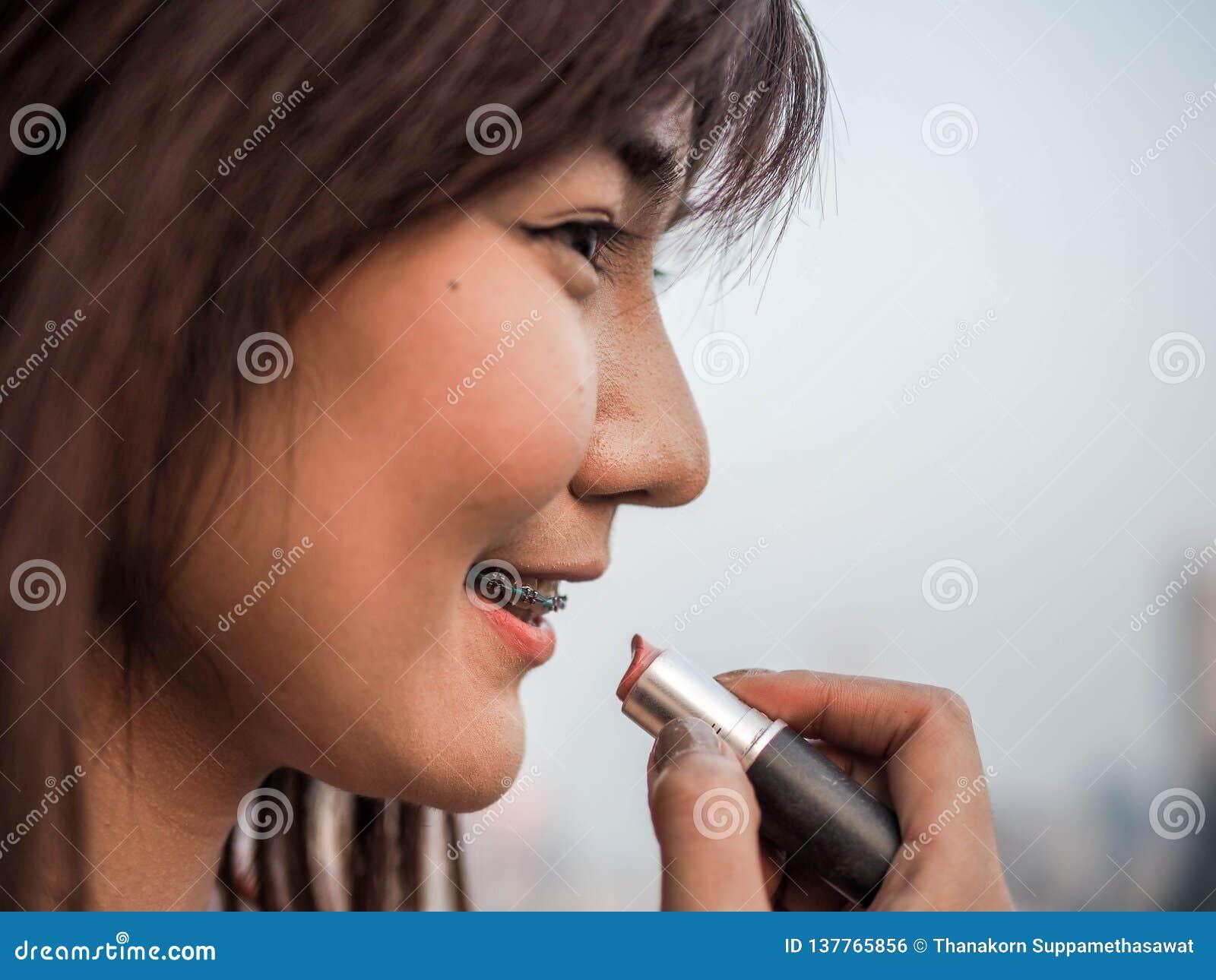 Slut upp den härliga asiatiska kvinnan som sätter makeupläppstift, lyckligt kvinnabegrepp som är filmiskt
