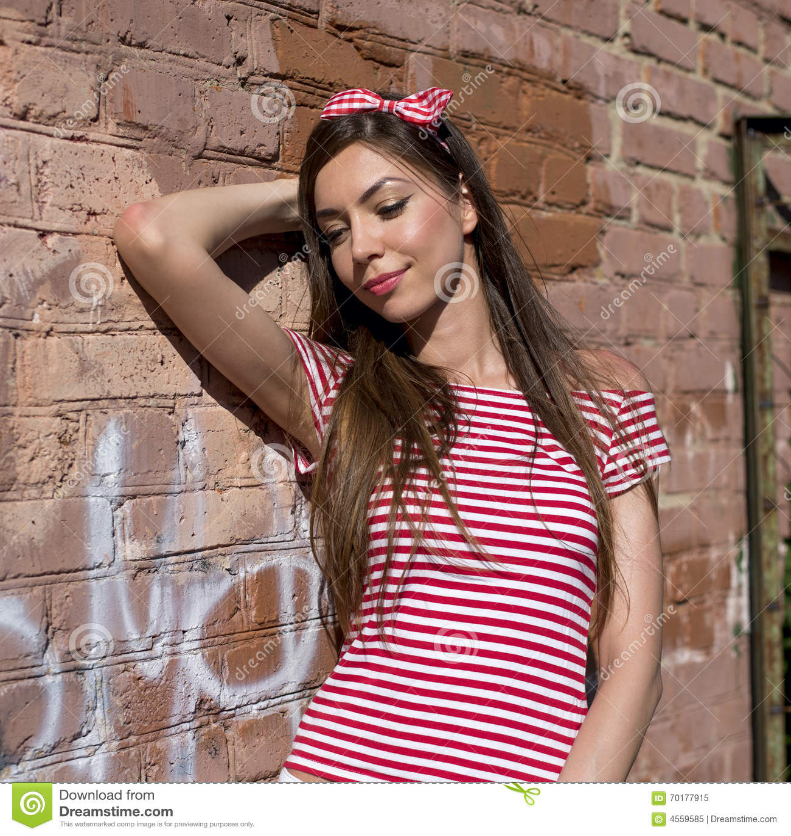 Slut upp den härliga flickan för livsstilmodestående som ler den stående near tegelstenväggen