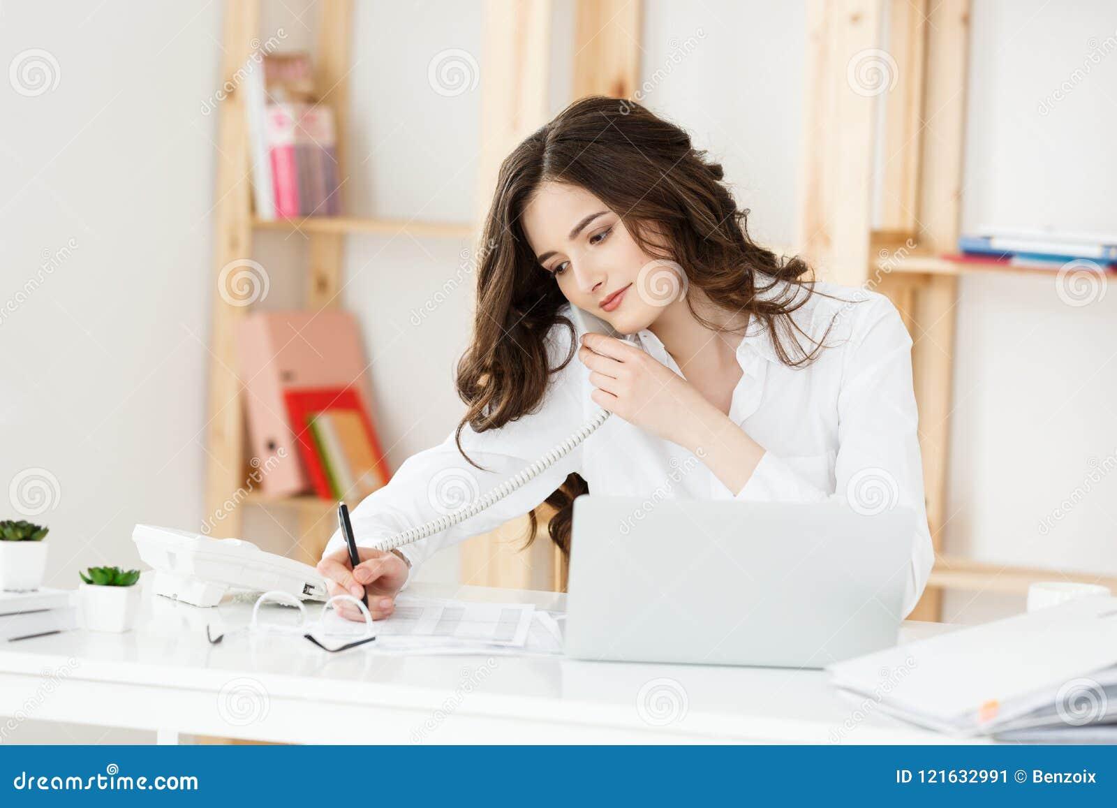 Slut upp den unga kontorskvinnan som talar till någon på hennes telefon, medan se in i avståndet med lyckligt ansiktsuttryck