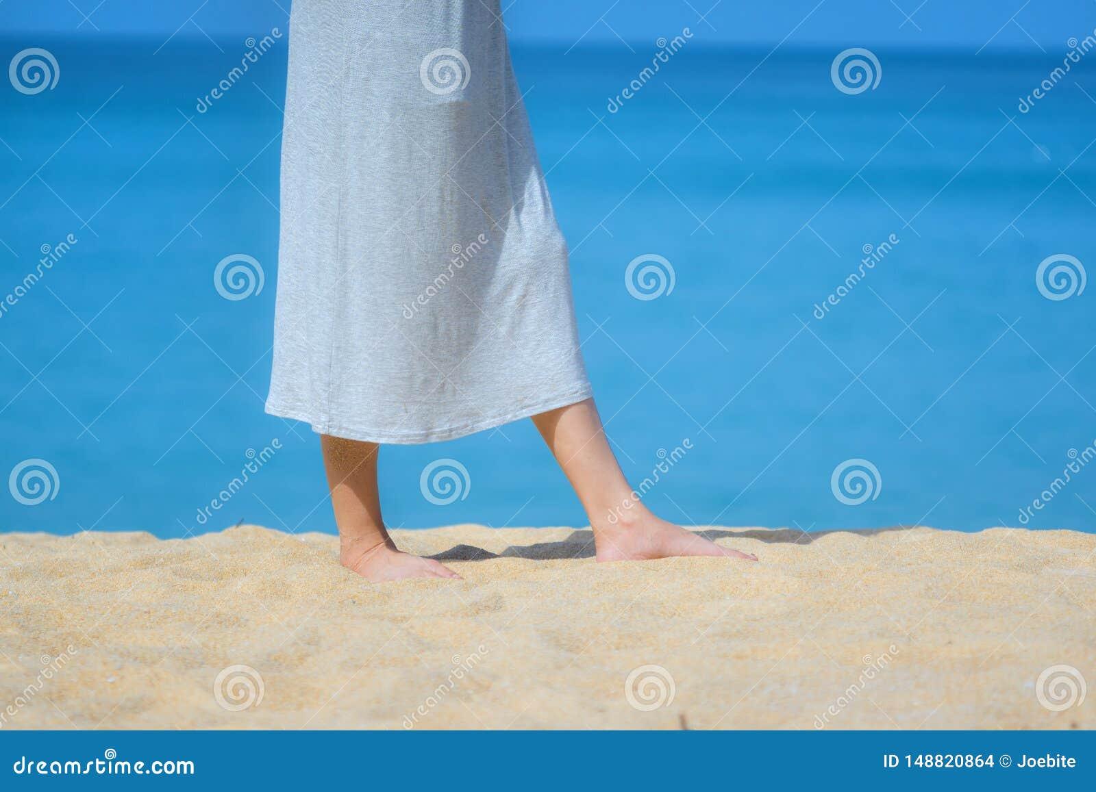 Slut upp h?rlig ung kvinnlig fot barfota som g?r p? sandstranden med havs- och himmelbakgrund Morgondet fria ?var i en su