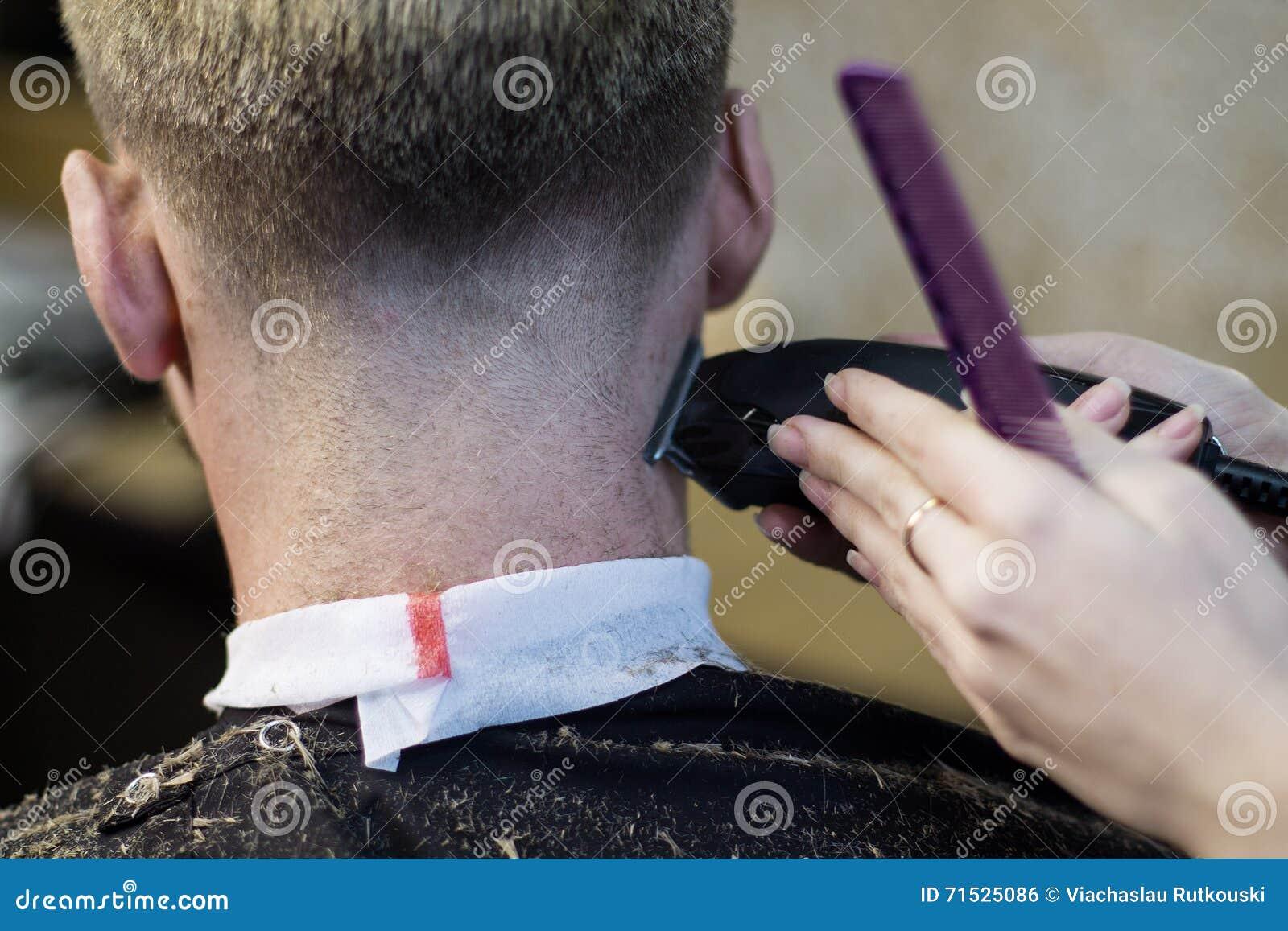 Slut upp kvinnas händer som gör mans frisyr