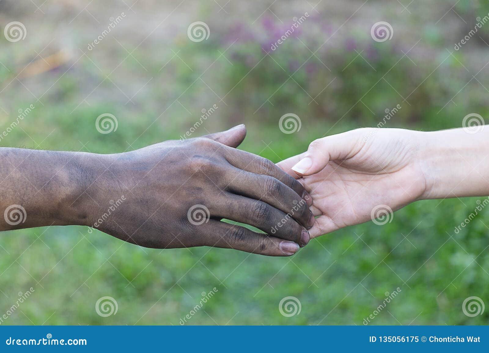 Slut upp man- och kvinnahänder som trycker på att rymma tillsammans på suddig bakgrund för begreppet för förälskelsevalentindag,