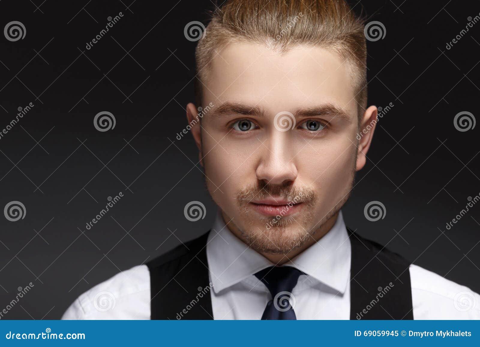 Slut upp ståenden av en mycket stilig ung man med gråa ögon