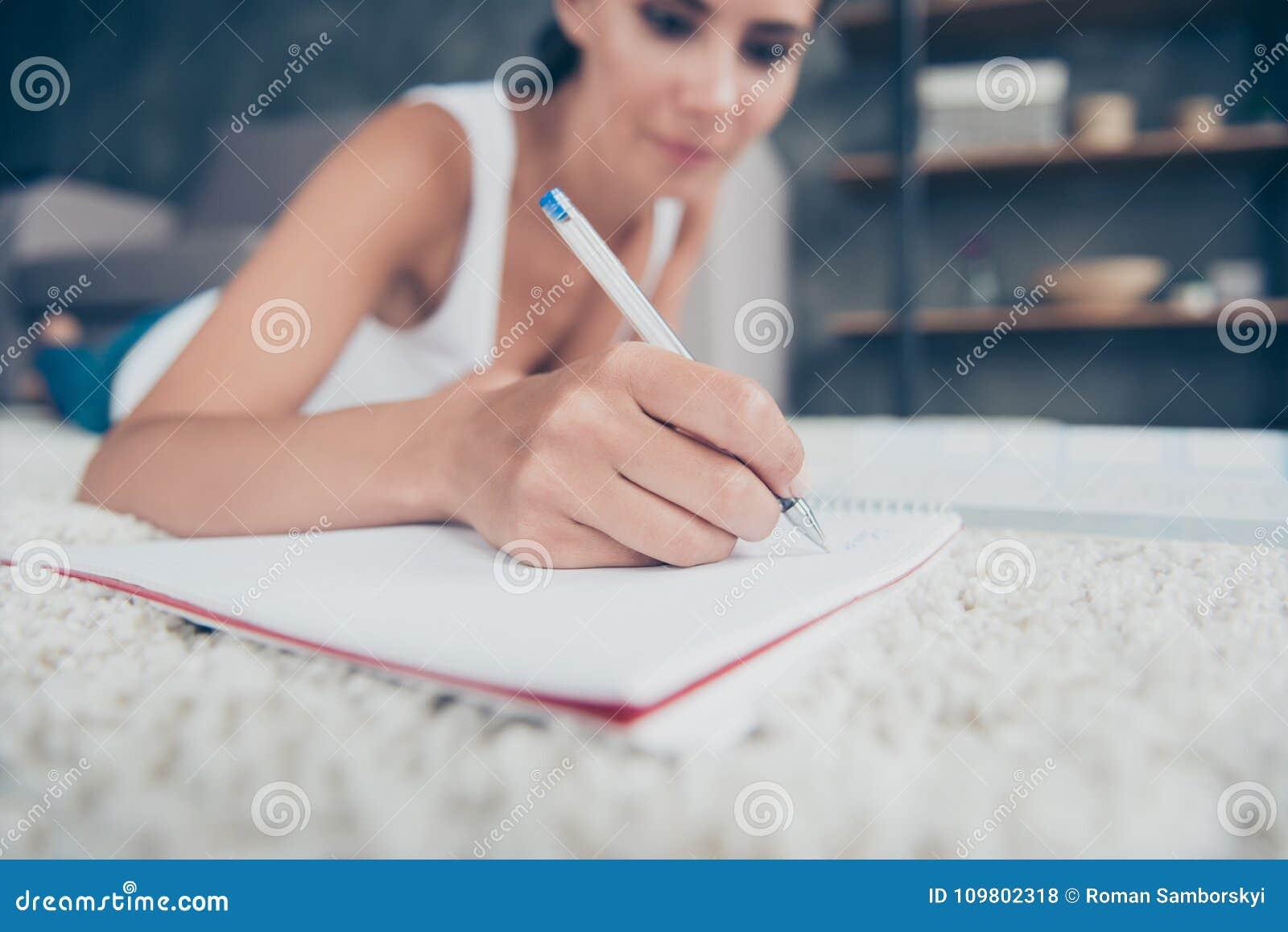 Slut upp ståenden av kvinnahanden med blyertspennahandstil i förskriftsbok,