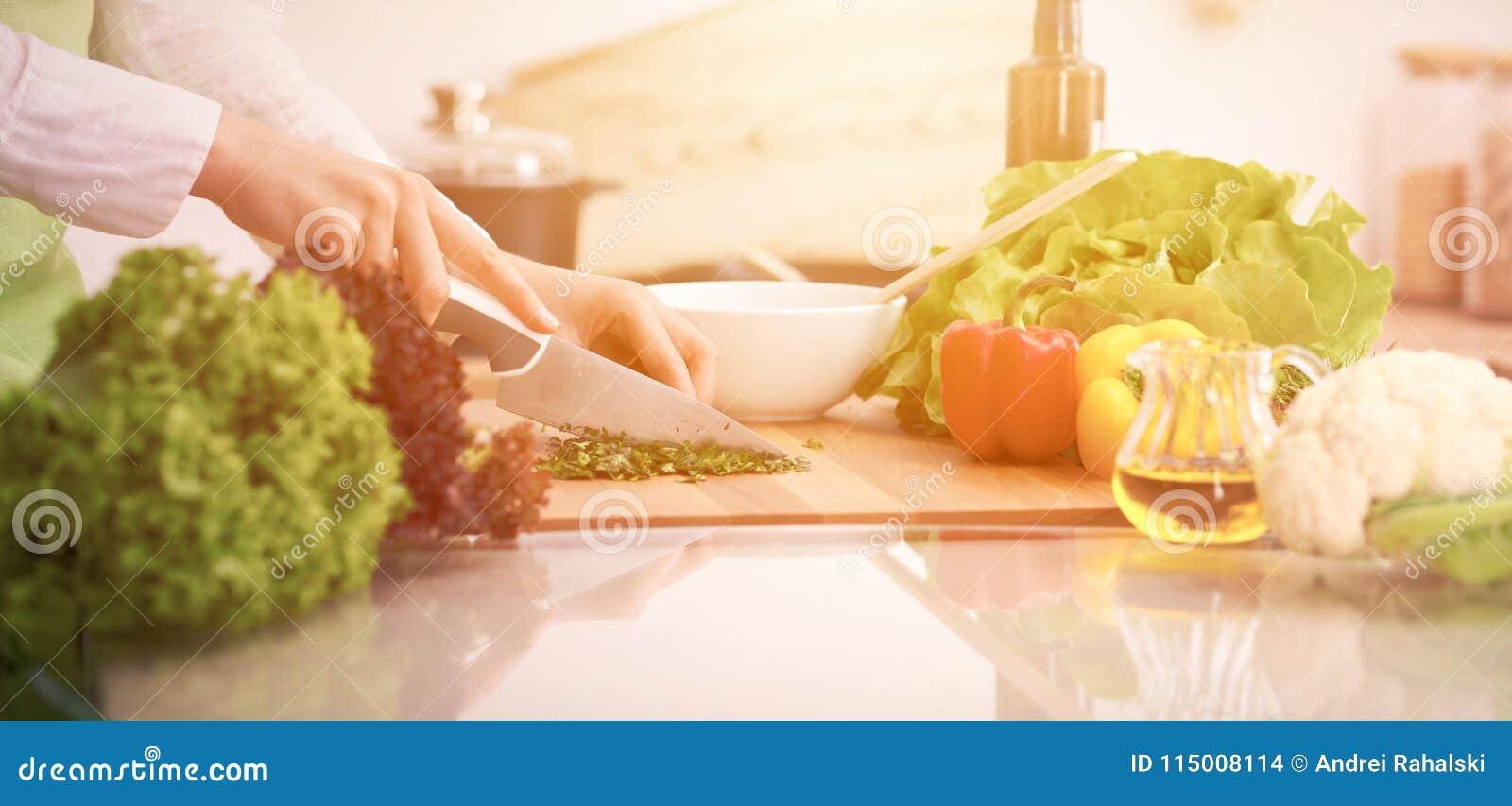 Slutet av människan räcker upp matlagninggrönsaksallad i kök på den glass tabellen med reflexion Sunt mål, och