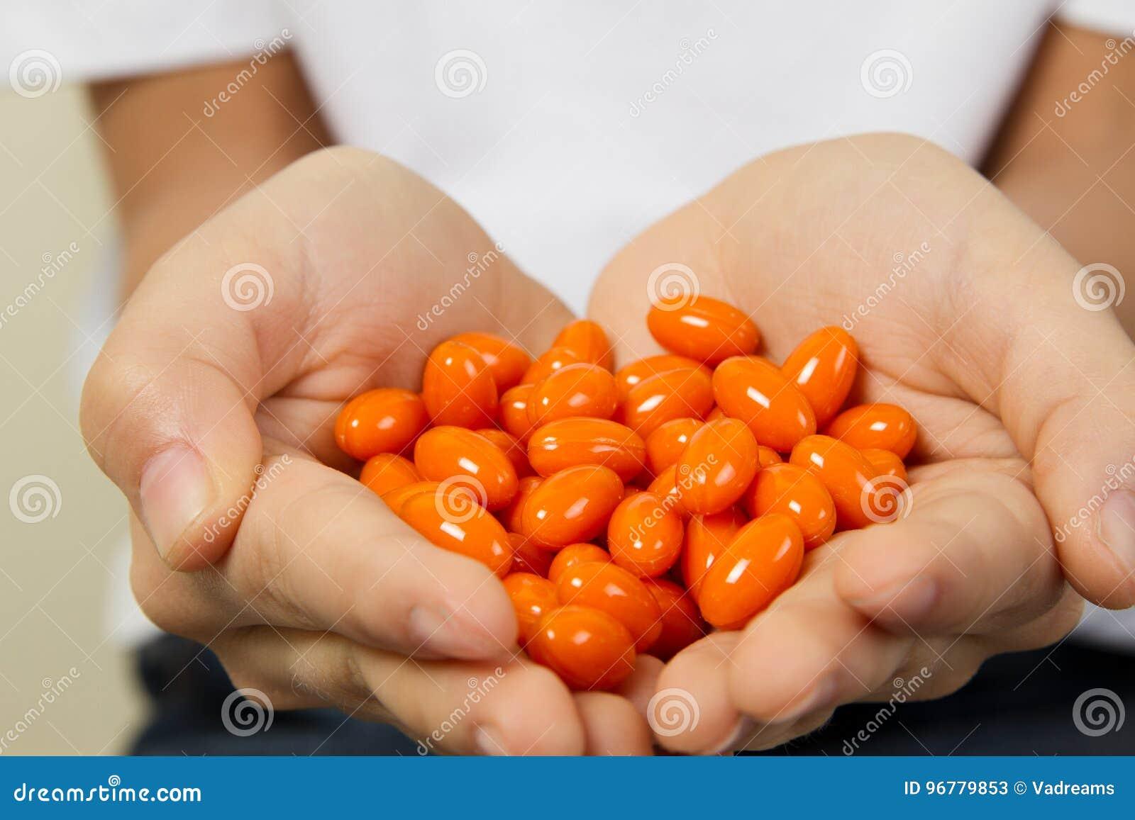 Slutet av ungen räcker upp att rymma många vitaminpreventivpillerar