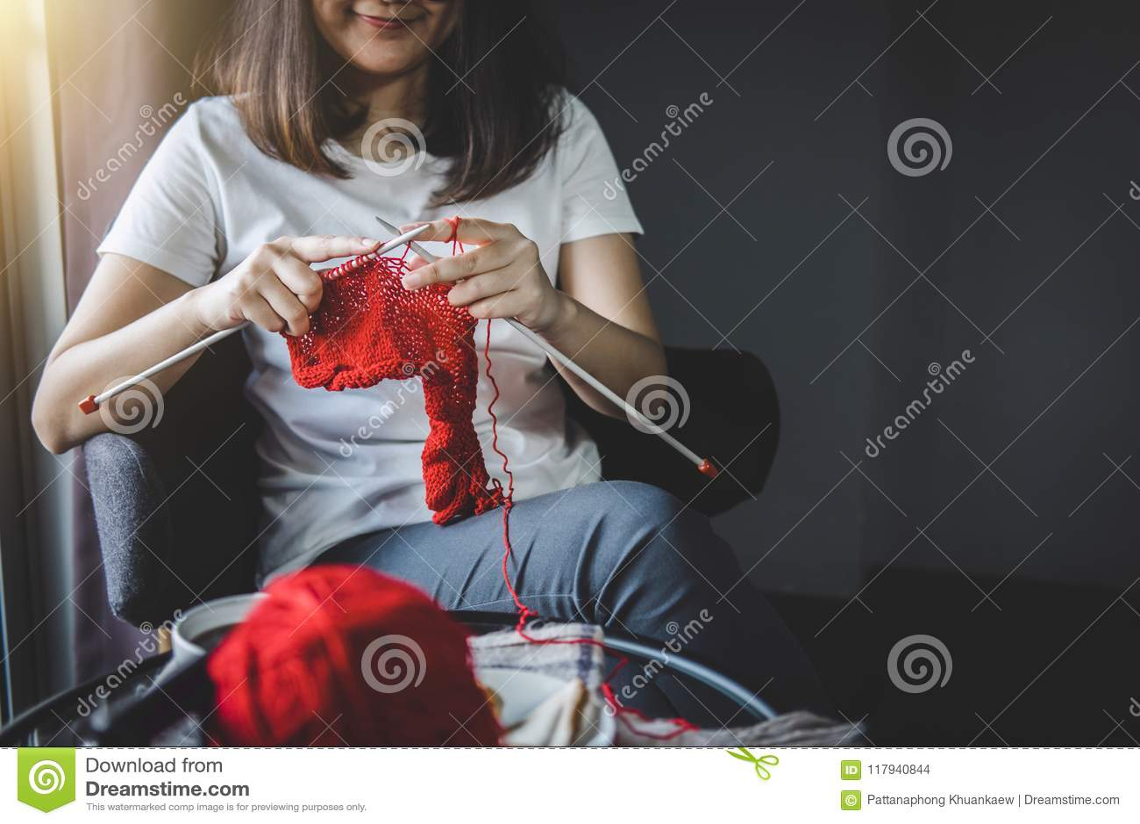 Slutet sköt upp av händer för den unga kvinnan som sticker en röd halsdukhandicra