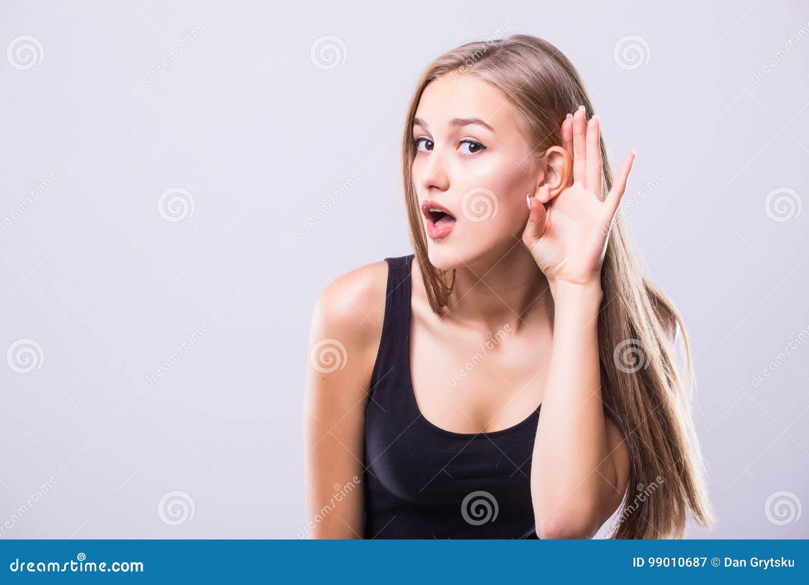 Slutet upp kvinna rymmer hennes hand nära gå i ax och lyssnar försiktigt isolerat på grå väggbakgrund Mänsklig sinnesrörelsekropp