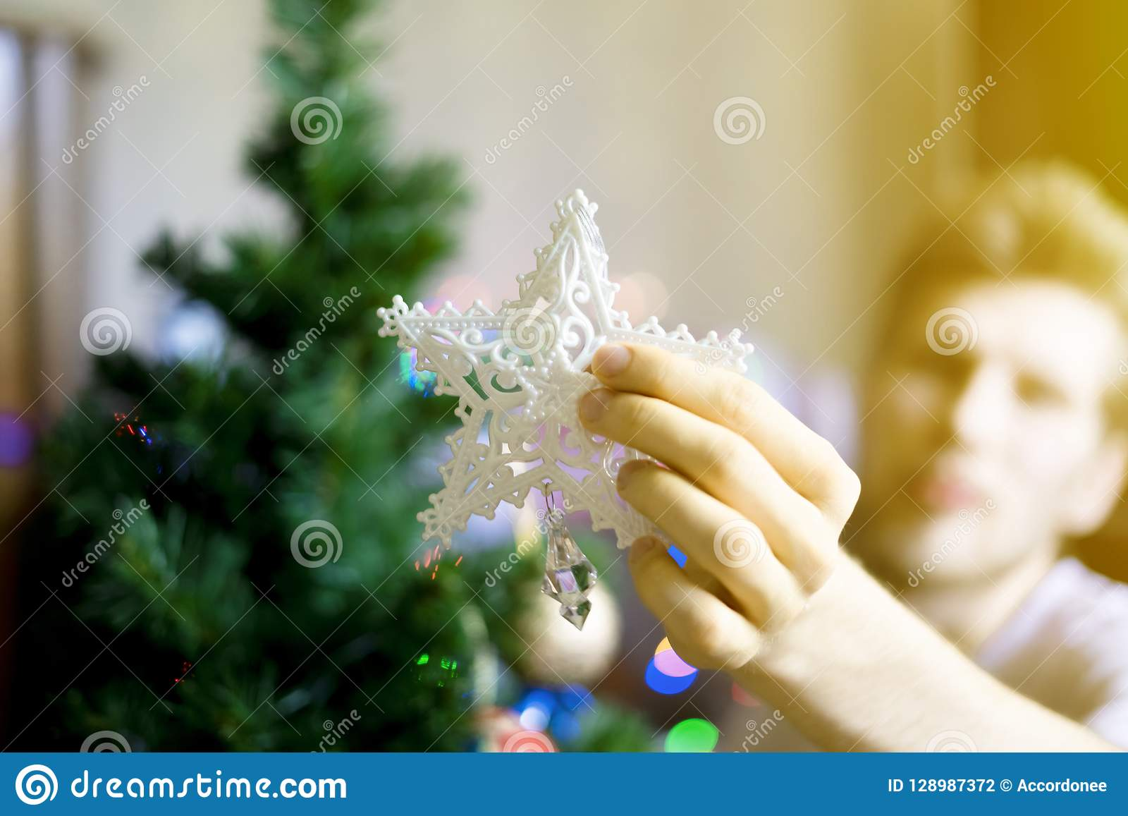 Slutet upp person` s räcker att sätta den vita garneringstjärnan överst av christmassträd f