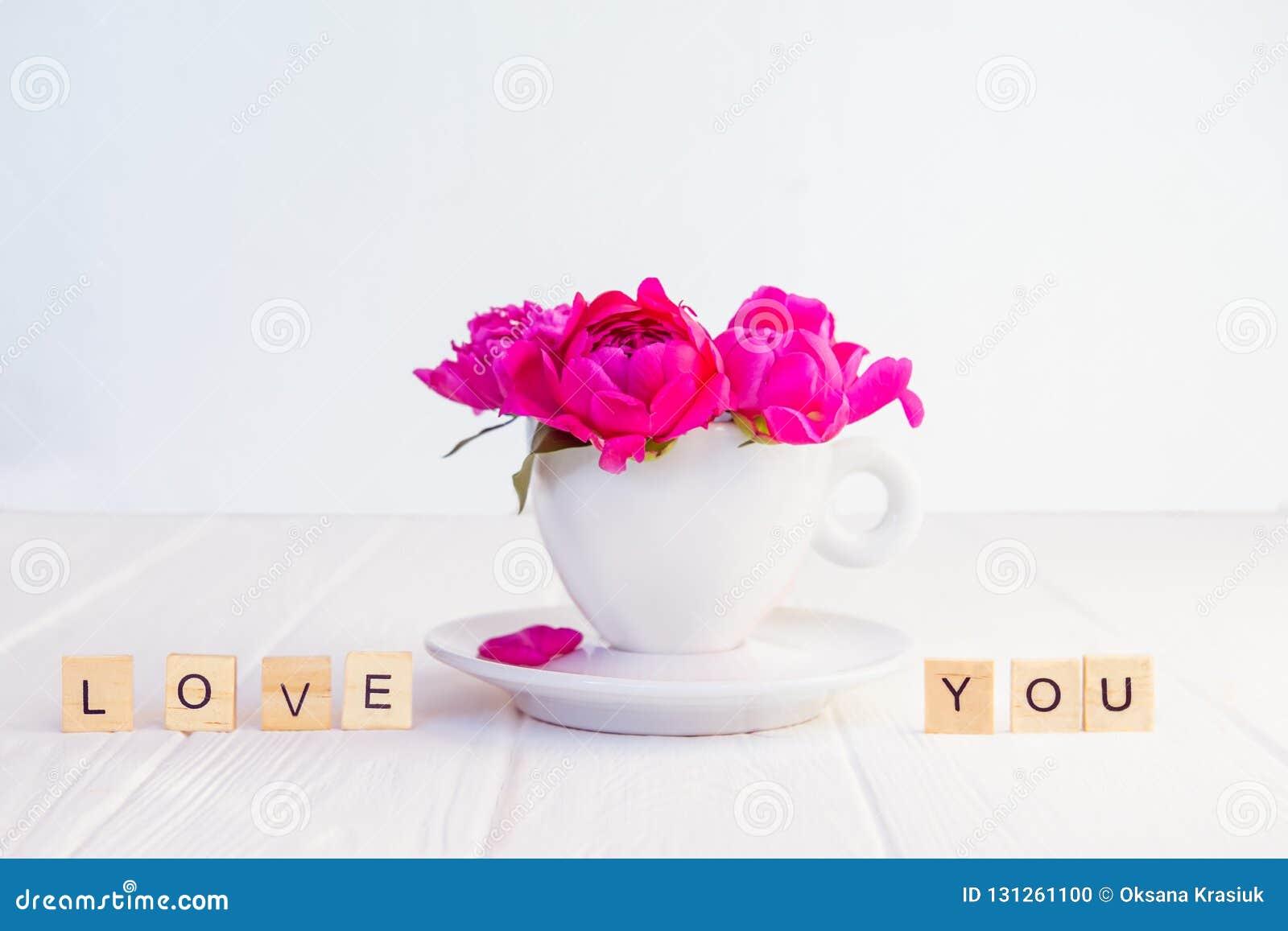 Slutet upp purpurfärgad rosa pionblommabukett i en dekorativt kopp och tefat och meddelande som jag älskar dig, stavade i träkvar