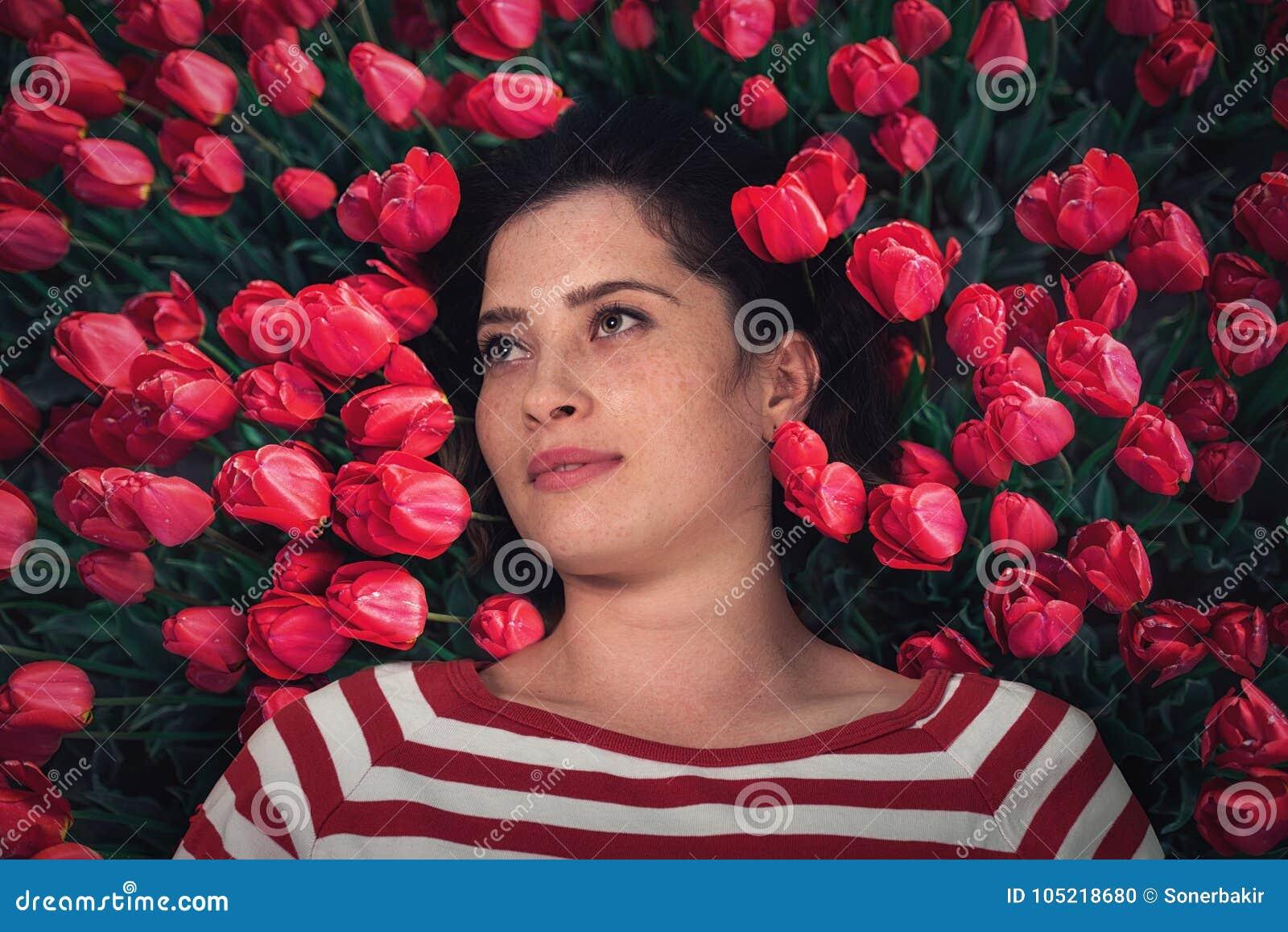 Slutet upp ståenden av den unga härliga flickakvinnan med rött brunt hår som ligger på gräs med den röda tulpan, blommar runt om