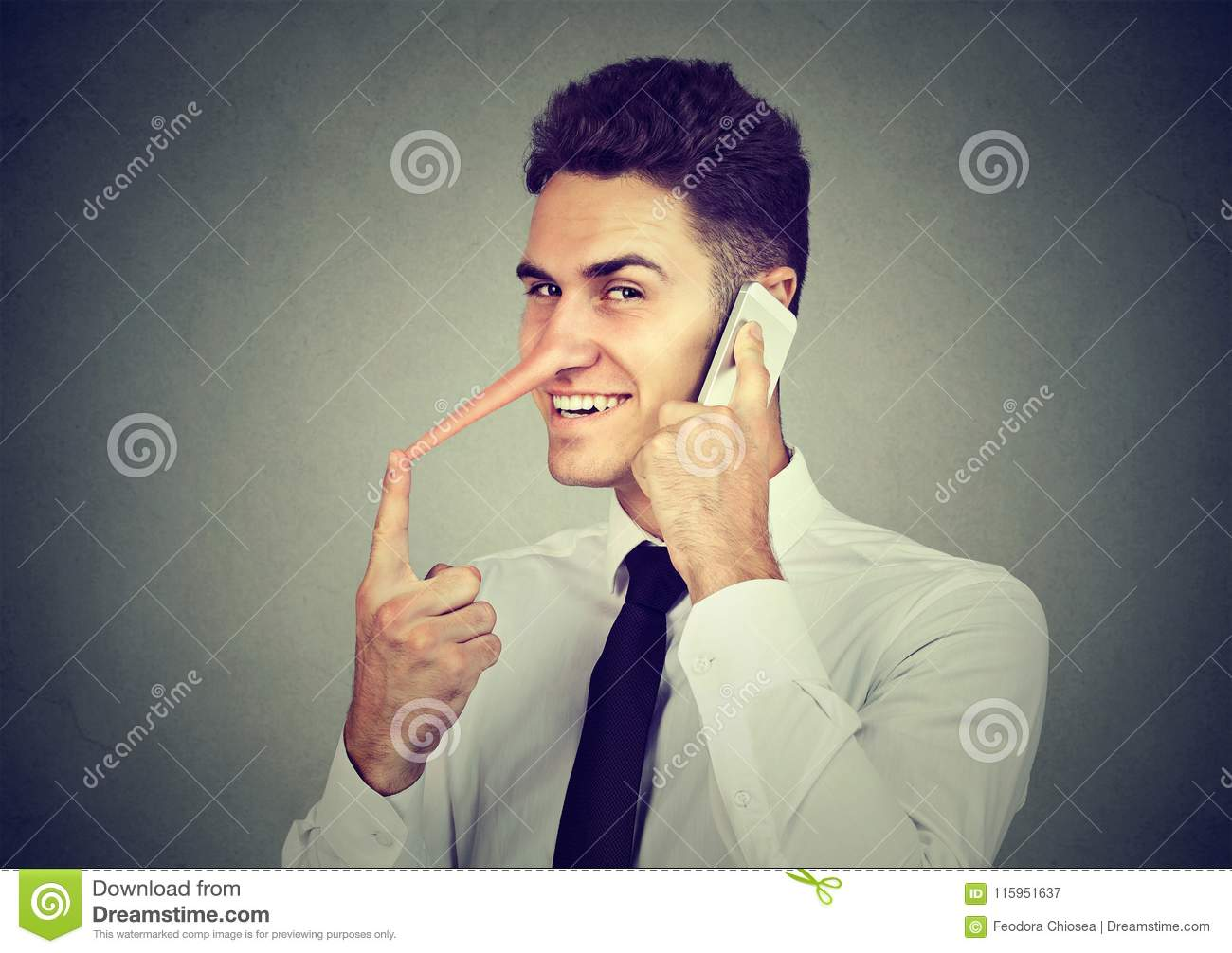 Sly young man with long nose talking on mobile phone on gray wall background. Liar concept.