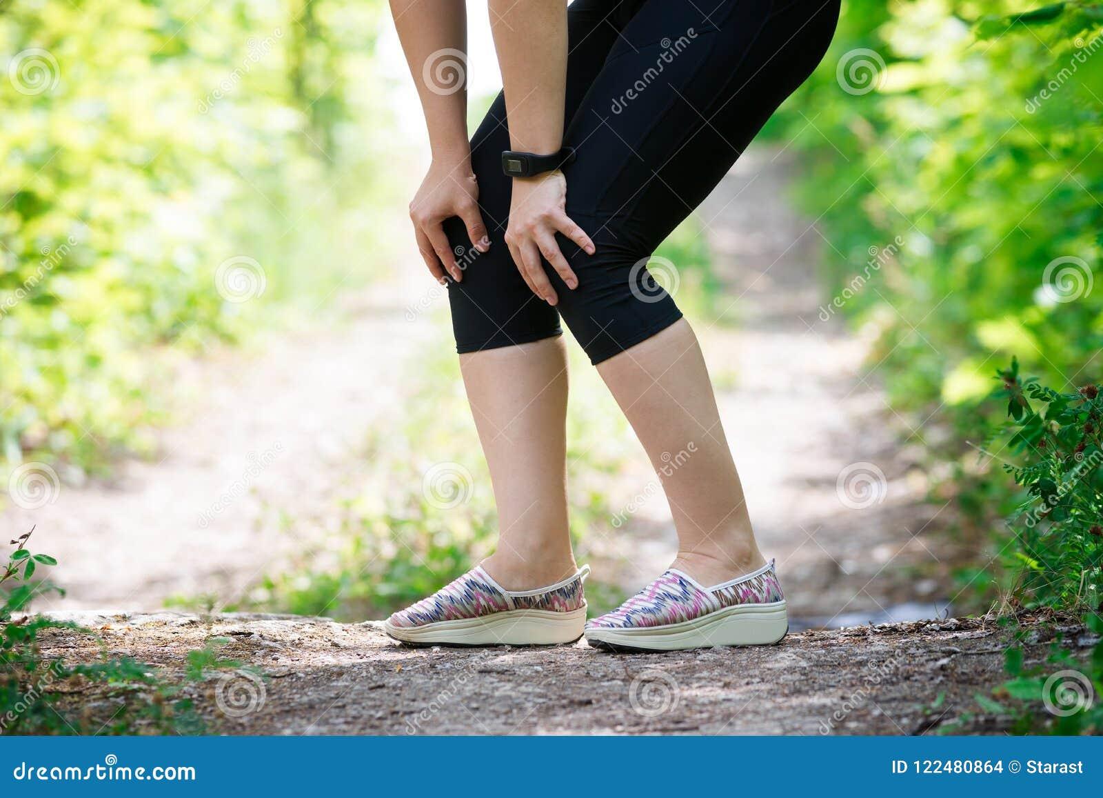 Smärta i knäet för kvinna` s, massage av det kvinnliga benet, skada, medan köra, trauman under genomkörare