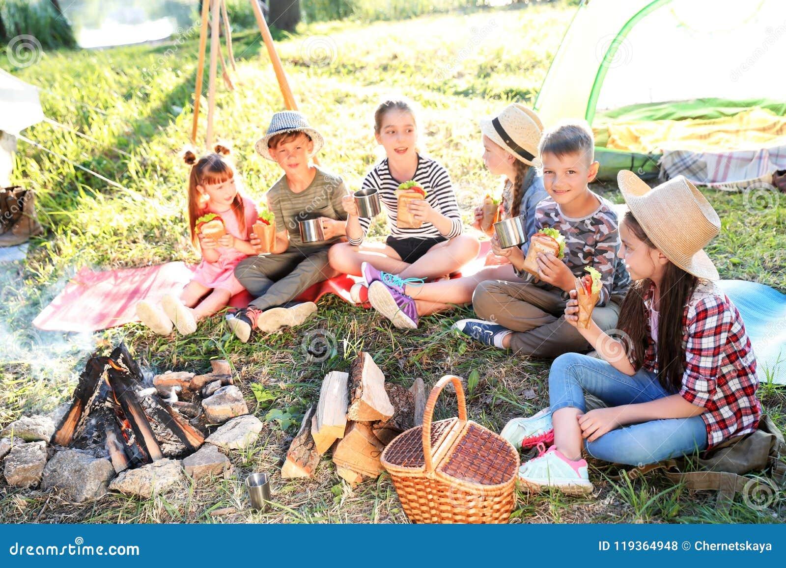 Små barn som äter smörgåsar, near brasan
