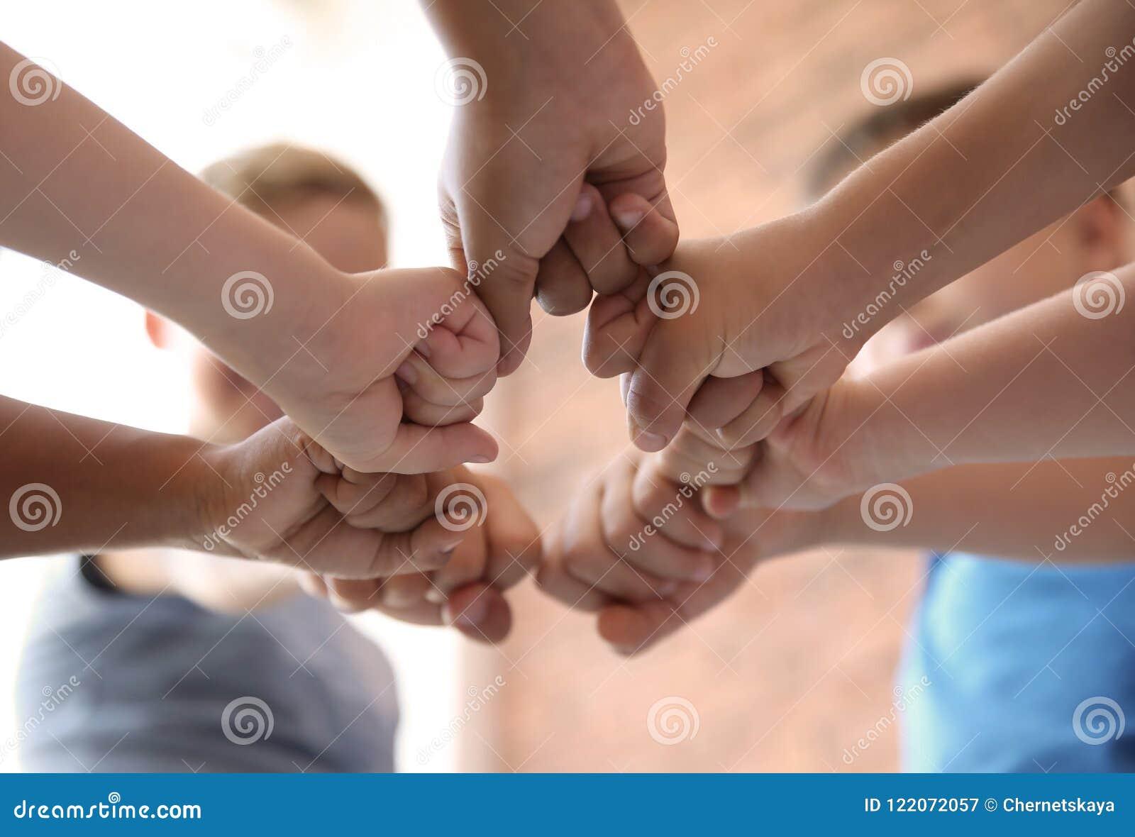 Små barn som tillsammans sätter deras händer