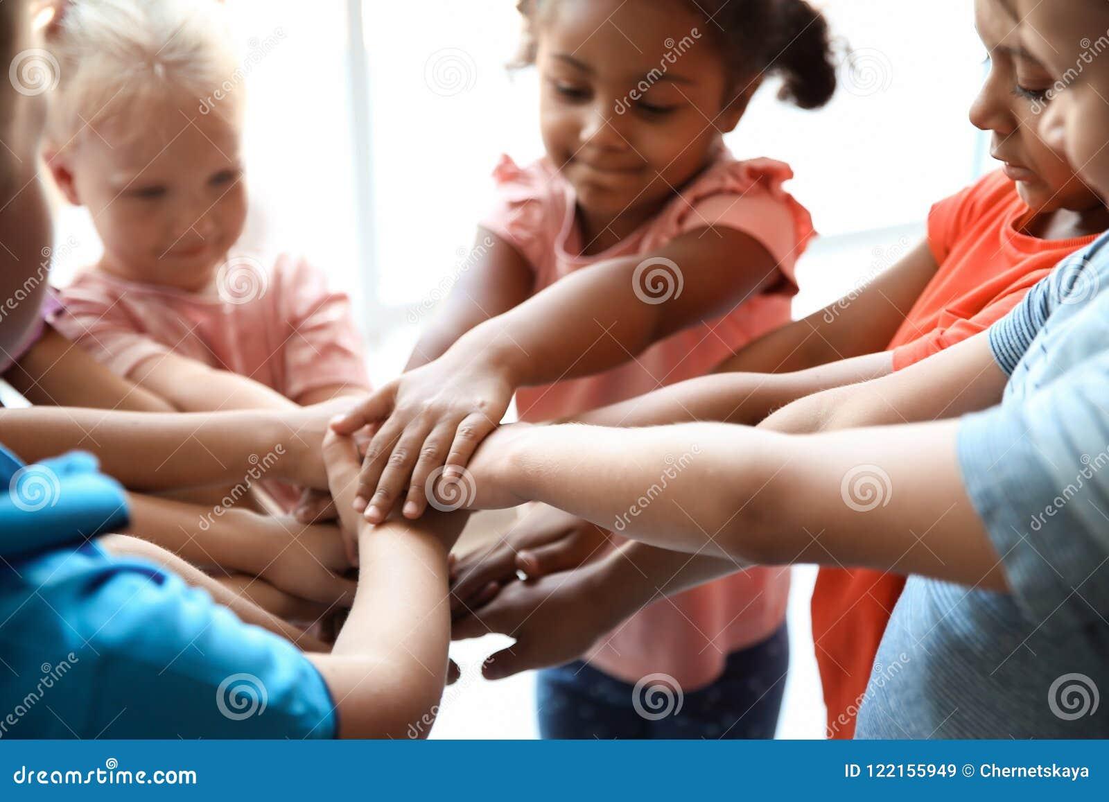 Små barn som tillsammans sätter deras händer, closeup
