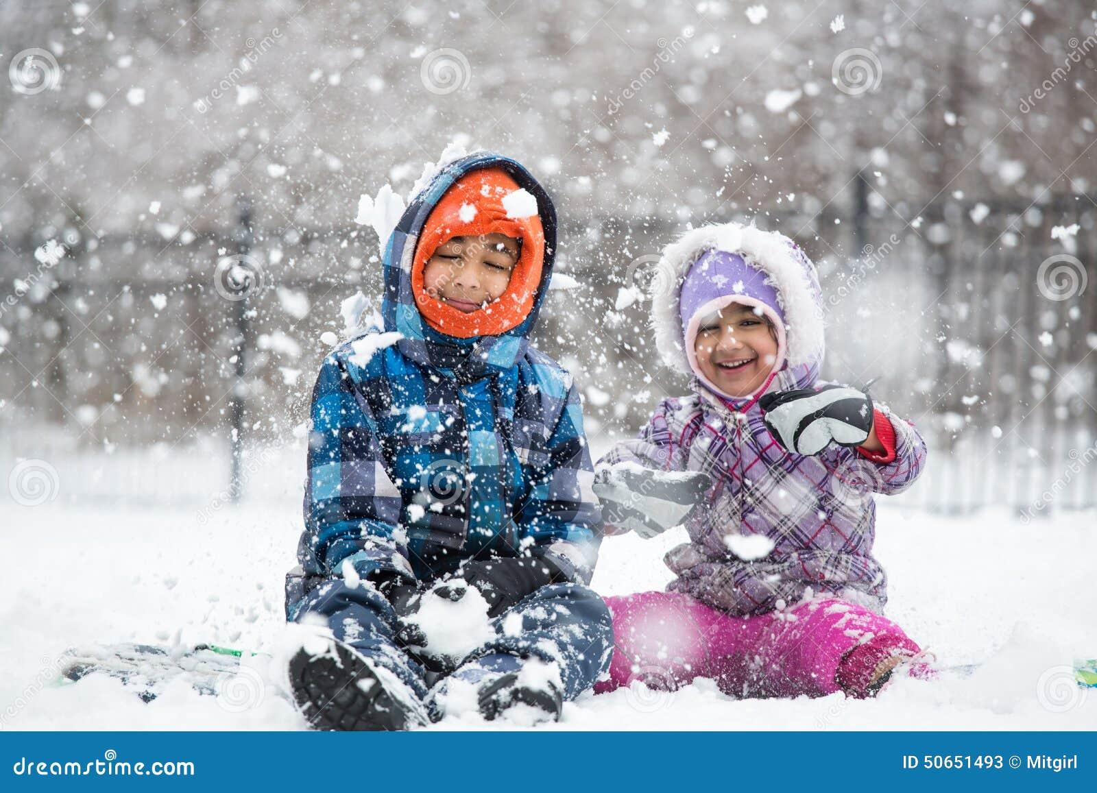 Små barn som tycker om snöfall