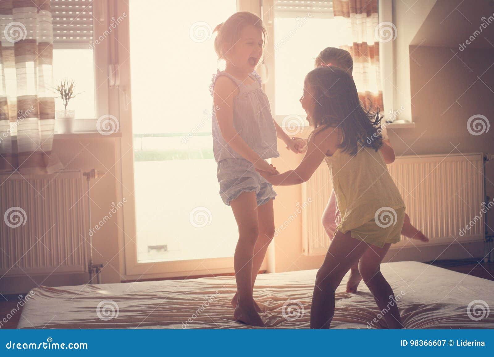 Små flickor som har gyckel tillsammans i säng