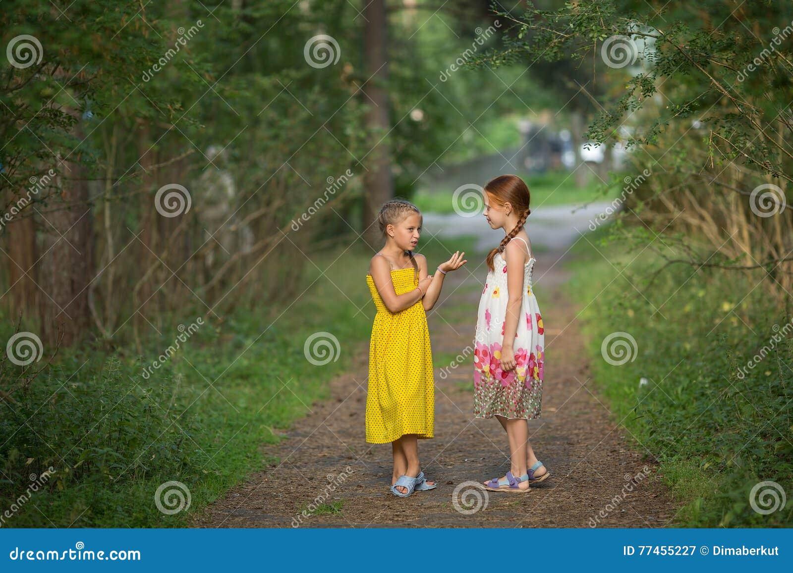 Små flickor som talar spännande att stå i den gröna gränden