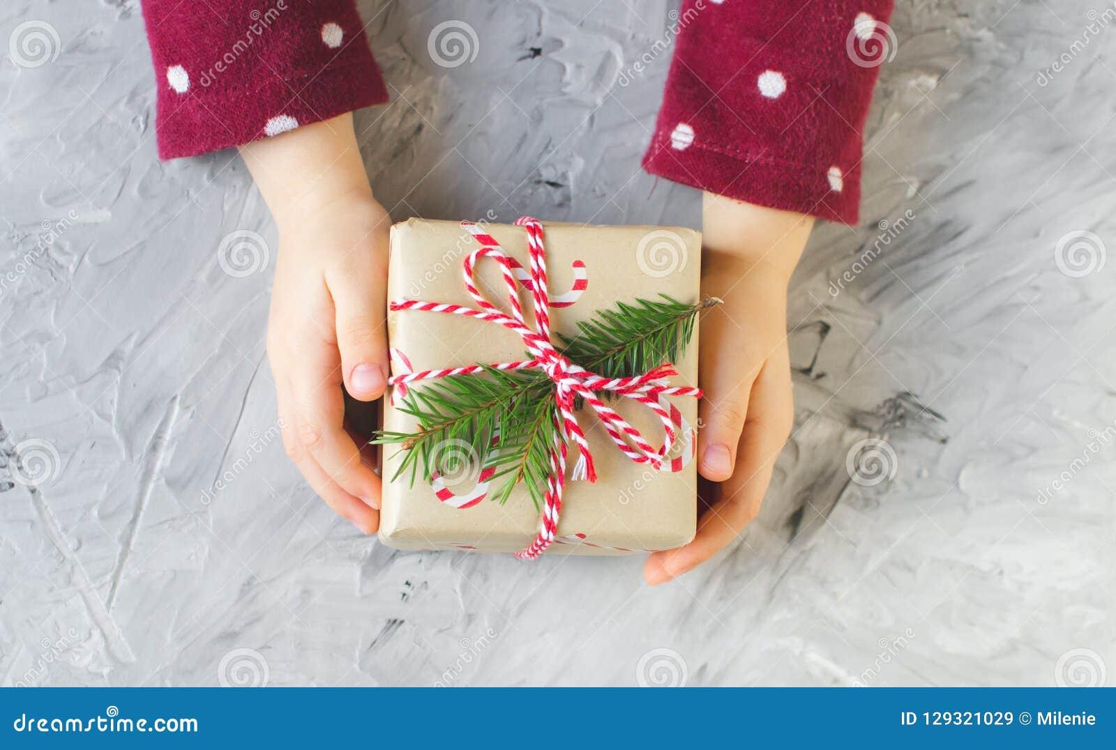 Små händer behandla som ett barn asken för gåvan för det nya året för jul för flickan den hållande, partibegrepp