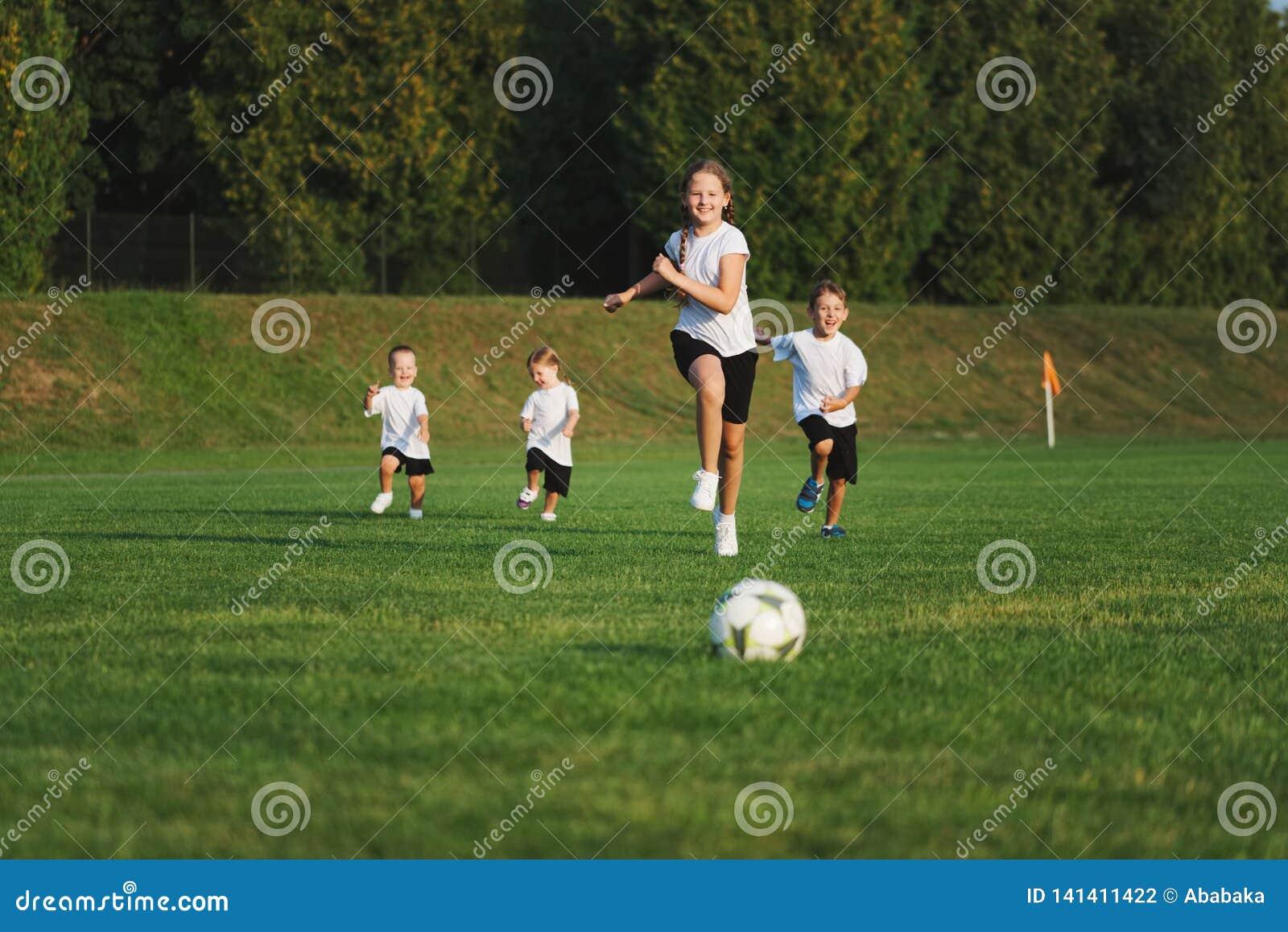 Små lyckliga barn på fotbollfält
