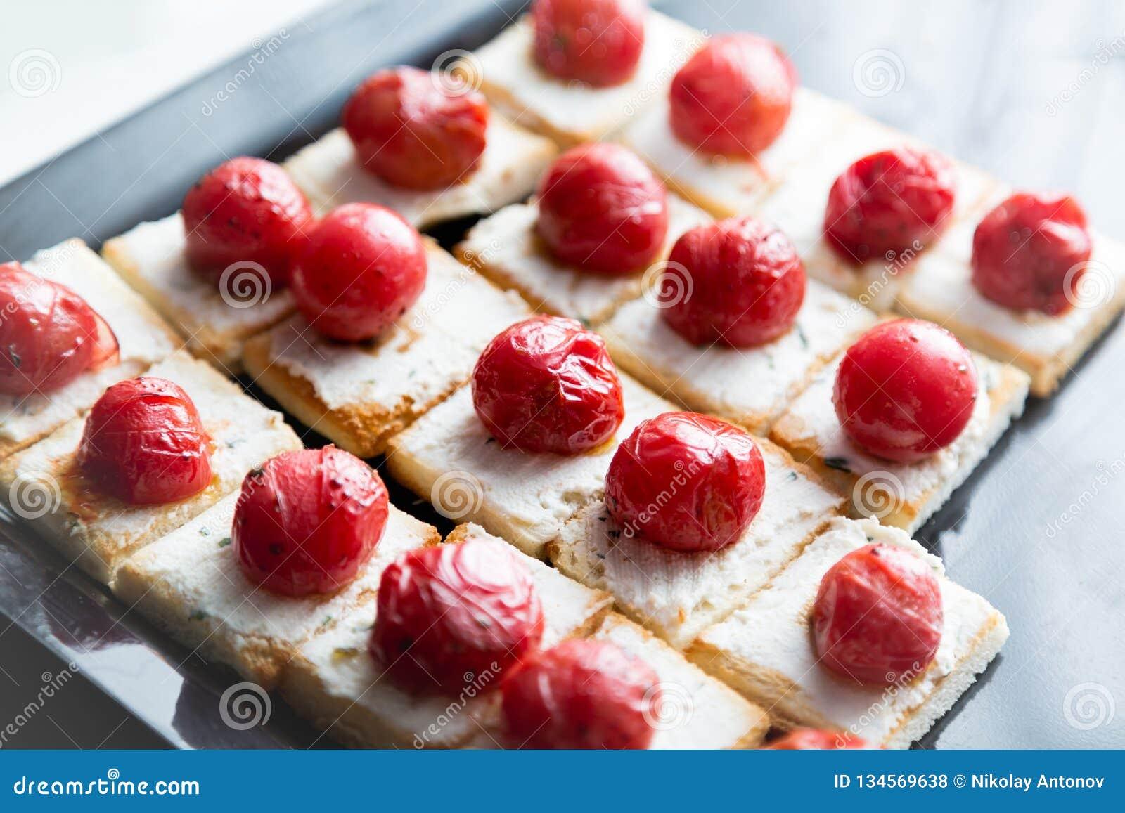 Små smörgåsar med ost och den grillade körsbärsröda tomaten Sköta om mat