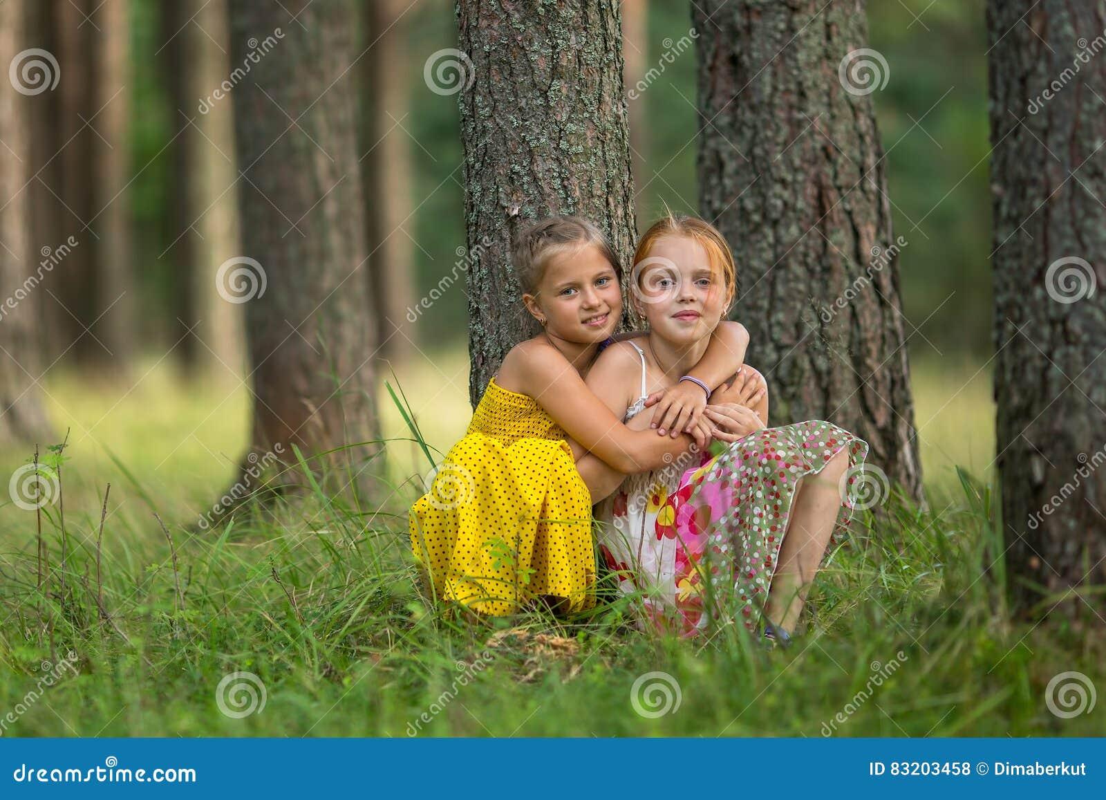 Små systrar sitter nära ett träd i parkera Natur