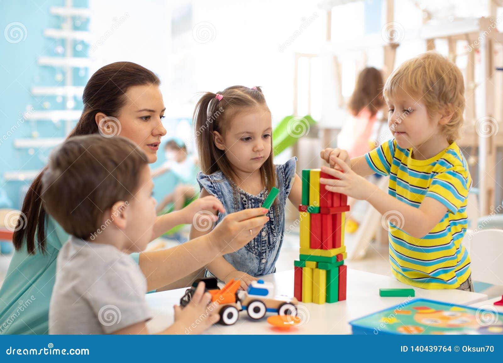 Små ungar bygger hemmastadd kvarterleksaker eller daycare Ungar som spelar med färgkvarter Bildande leksaker för förträning och d