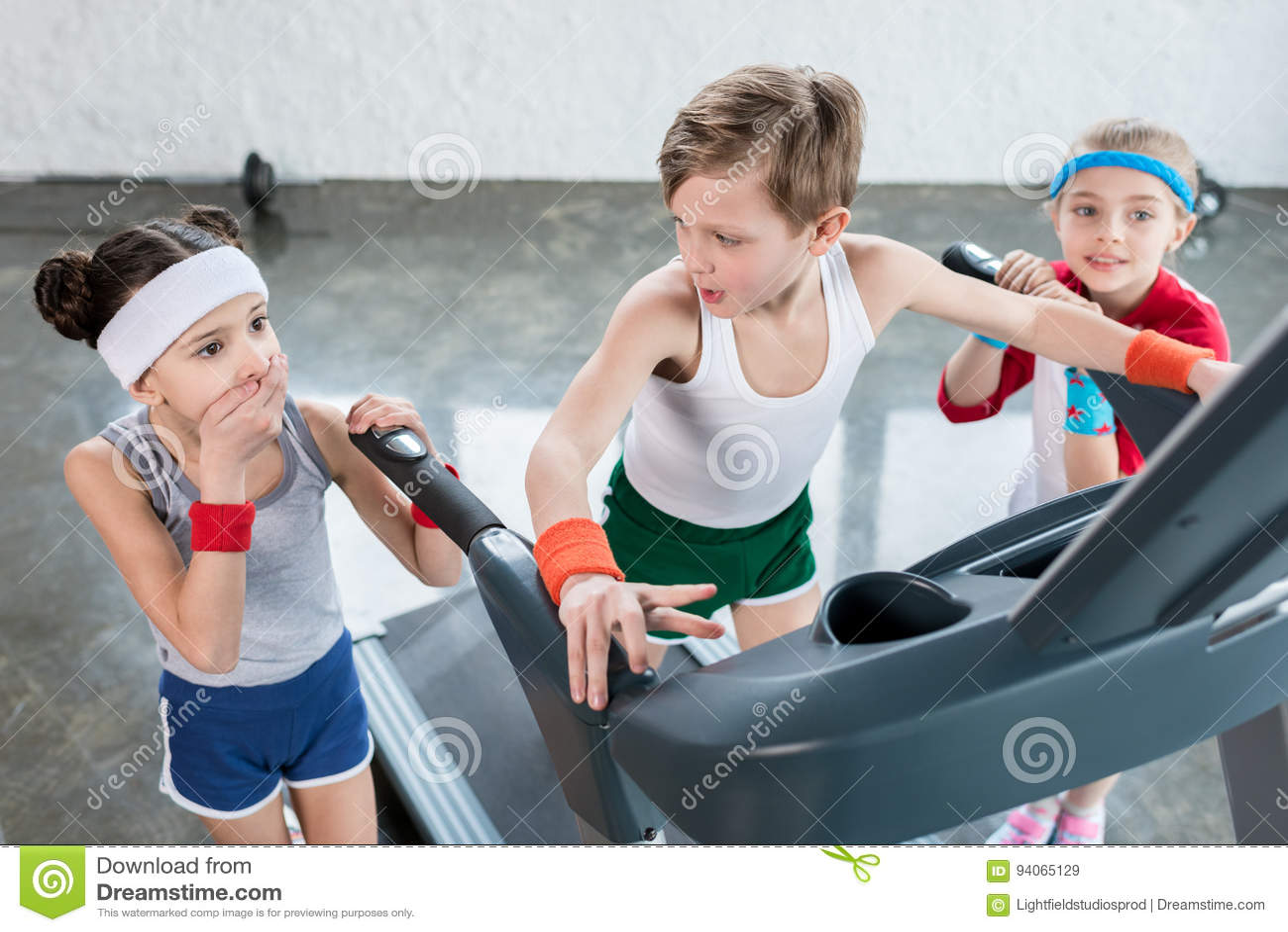 Små ungar i sportswear som övar på trampkvarnen i idrottshallen, begrepp för barnsportskola