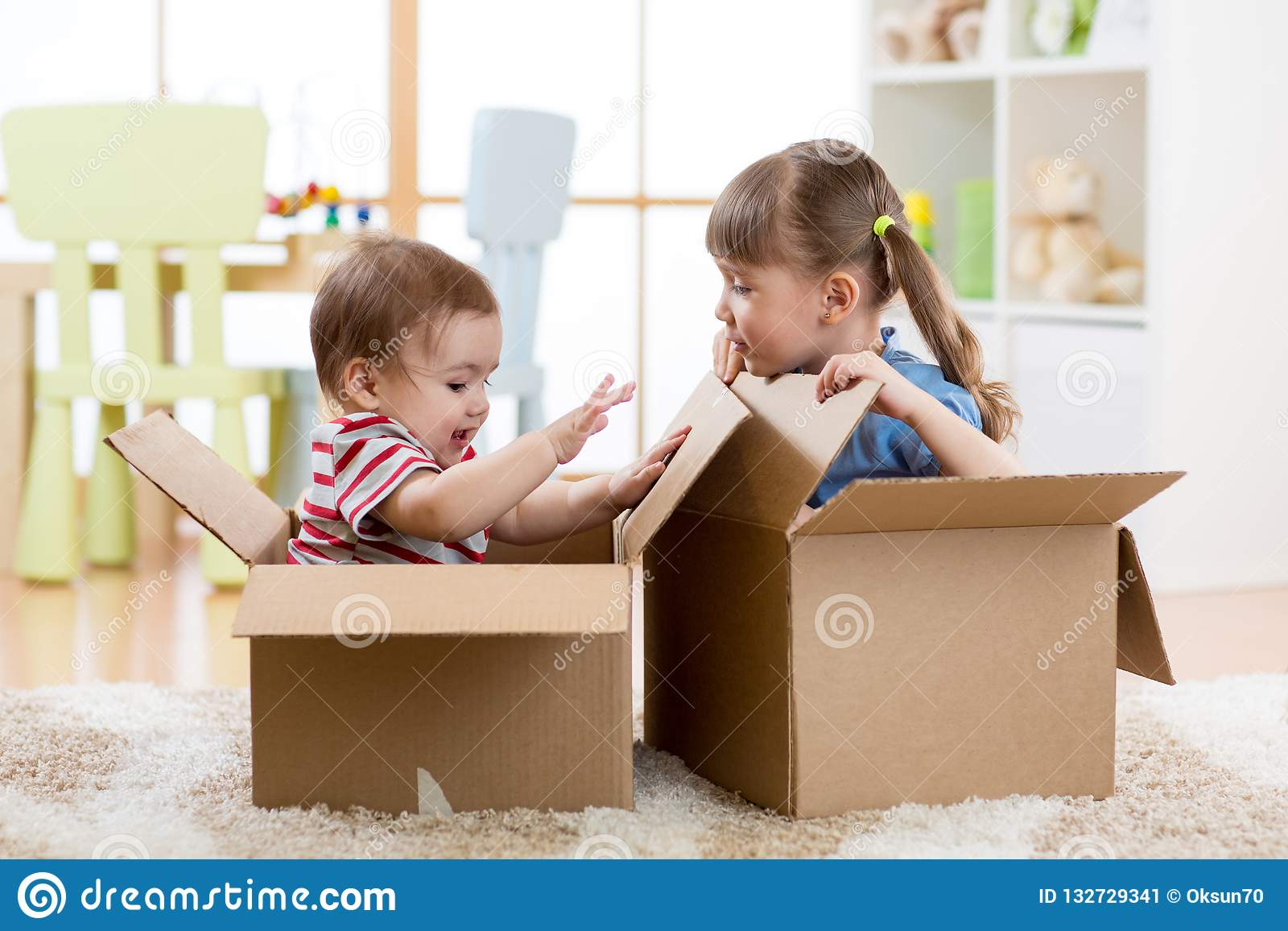 Små ungar pojke och flicka som spelar i kartonger barngyckel har