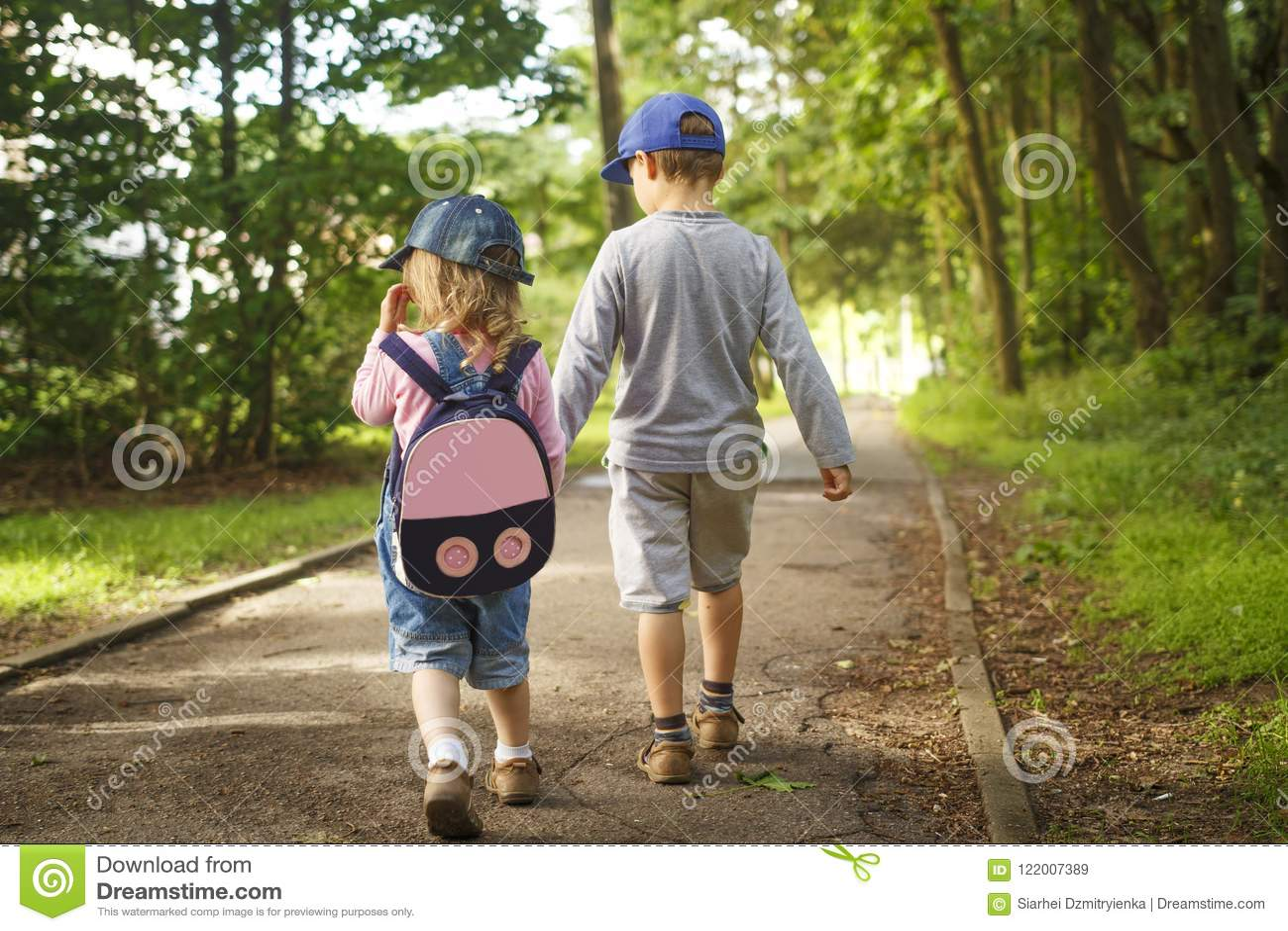 Små vänbarn rymmer händer och promenerar banan parkerar in på sommardag pojken och flickan går in parkerar utomhus