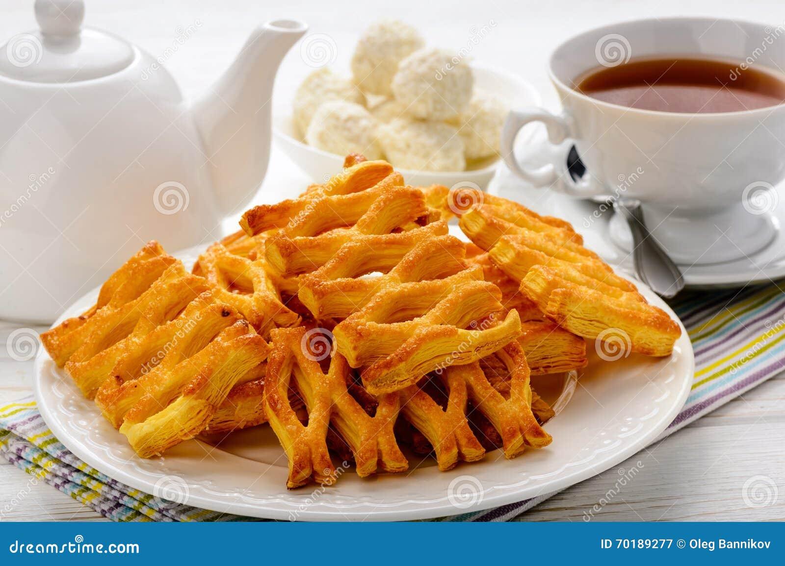 Smördegar, kopp te och tekanna på den vita trätabellen