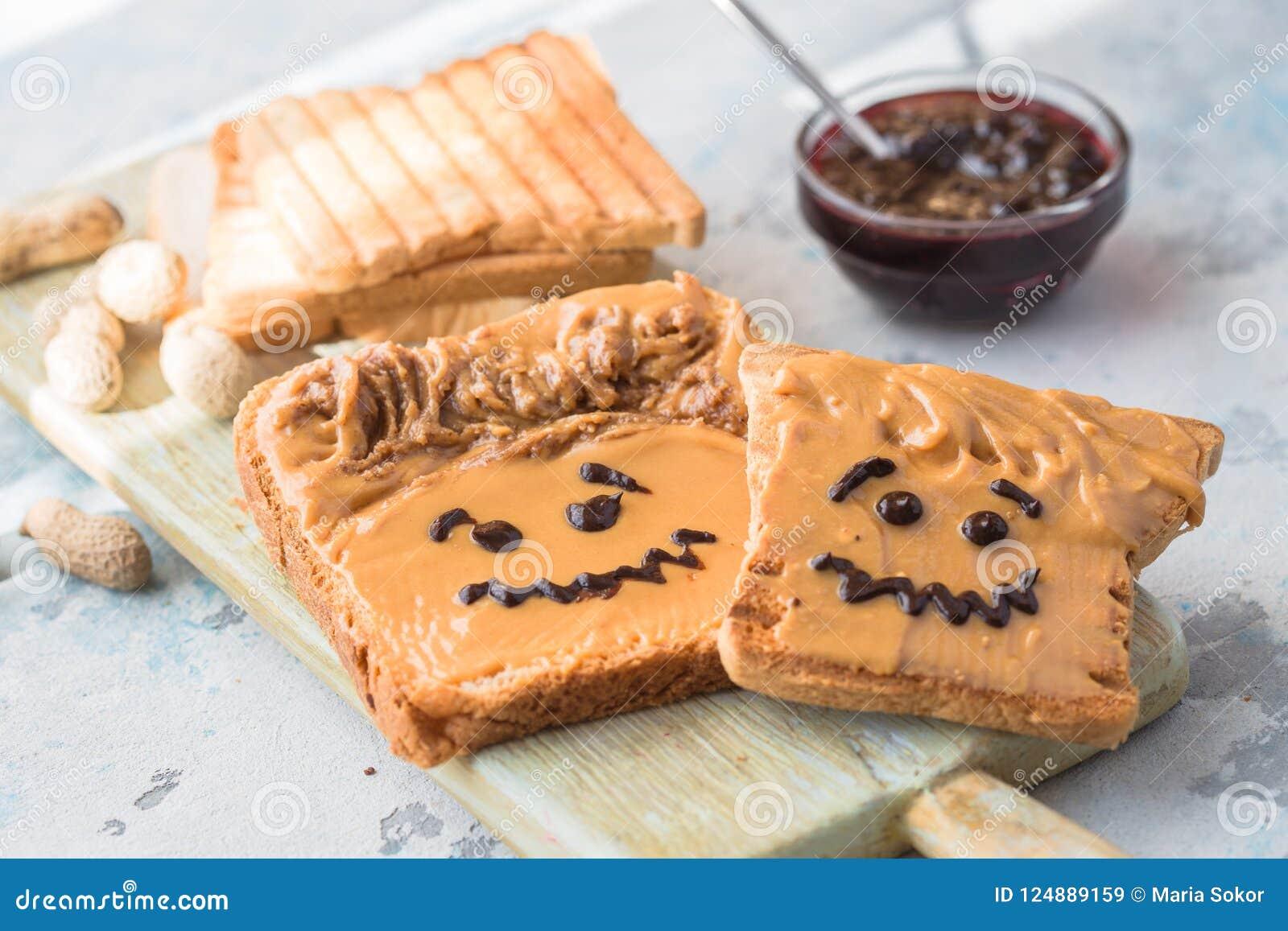 Smörgåsar för danandejordnötsmör med personlighet! Rolig smileyframsida som dras på med driftstopp Krämigt jordnötsmör med drifts