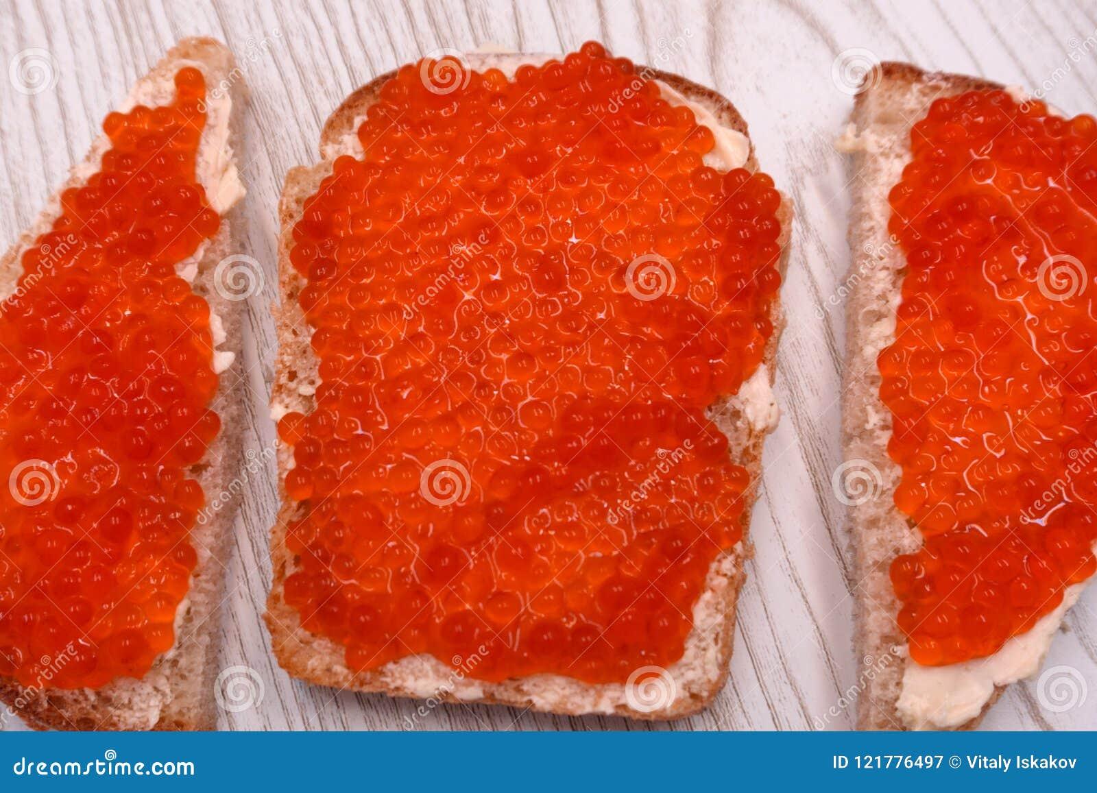Smörgåsar i form av hjärtor med kaviaren och smör för röd lax på rågbröd, bästa sikt