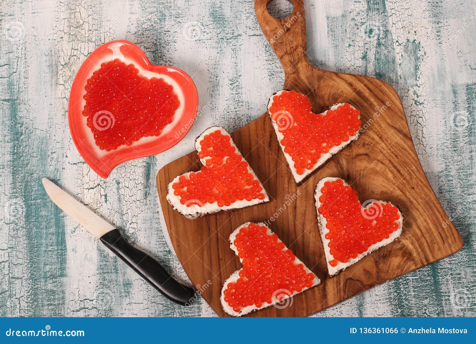 Smörgåsar med den röda kaviaren och gräddost i formen av en hjärta för valentin dag