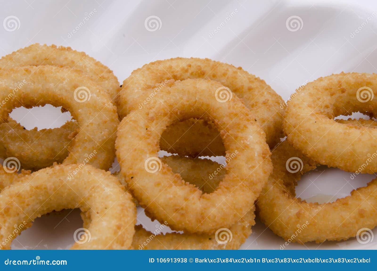 Smażący cebulkowi pierścionki w bielu talerzu na białym tle
