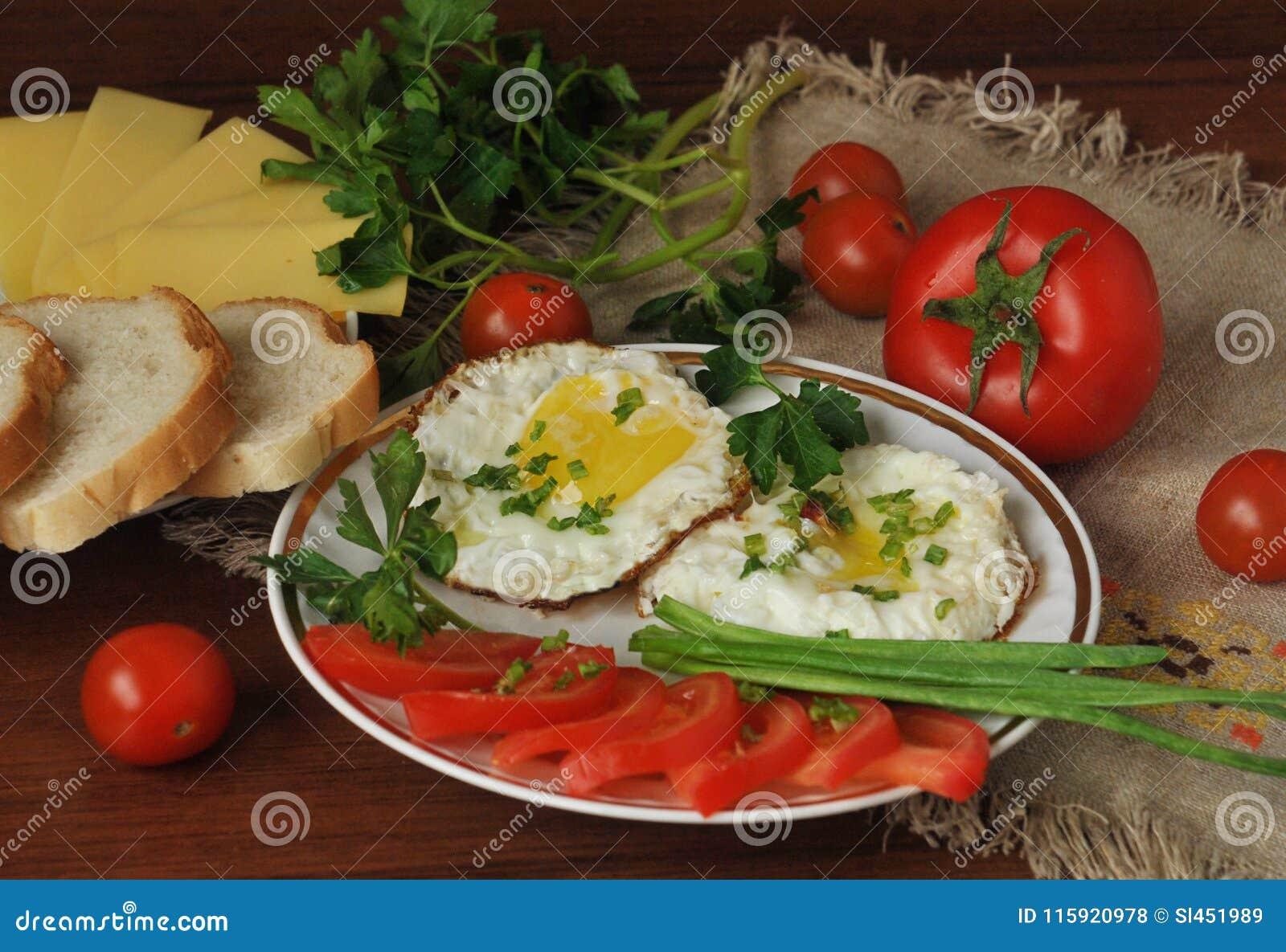 Smażący jajka, dojrzali czereśniowi pomidory i świezi ziele, Serowy i biały chleb