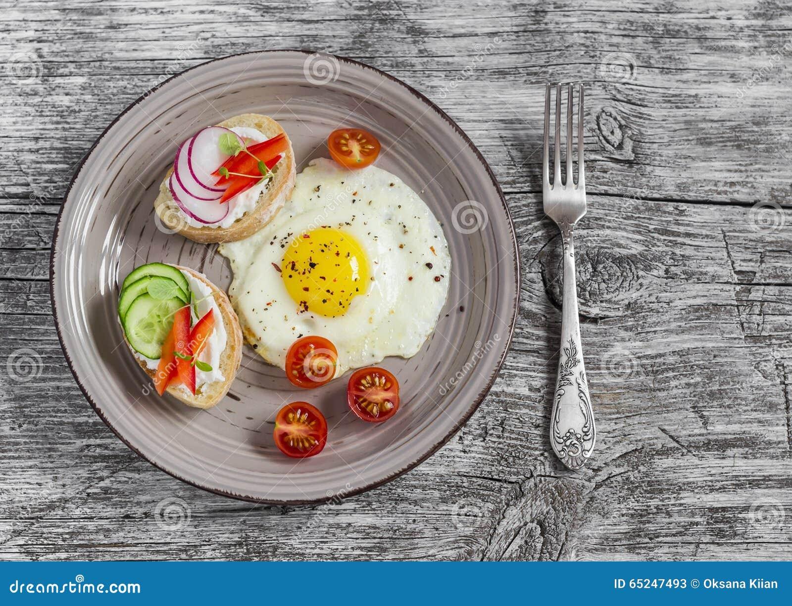 Smażący jajka, pomidory i kanapki z, ogórkiem, rzodkwią i miękkim serem, Na lekkim drewnianym stole Wieśniaka styl
