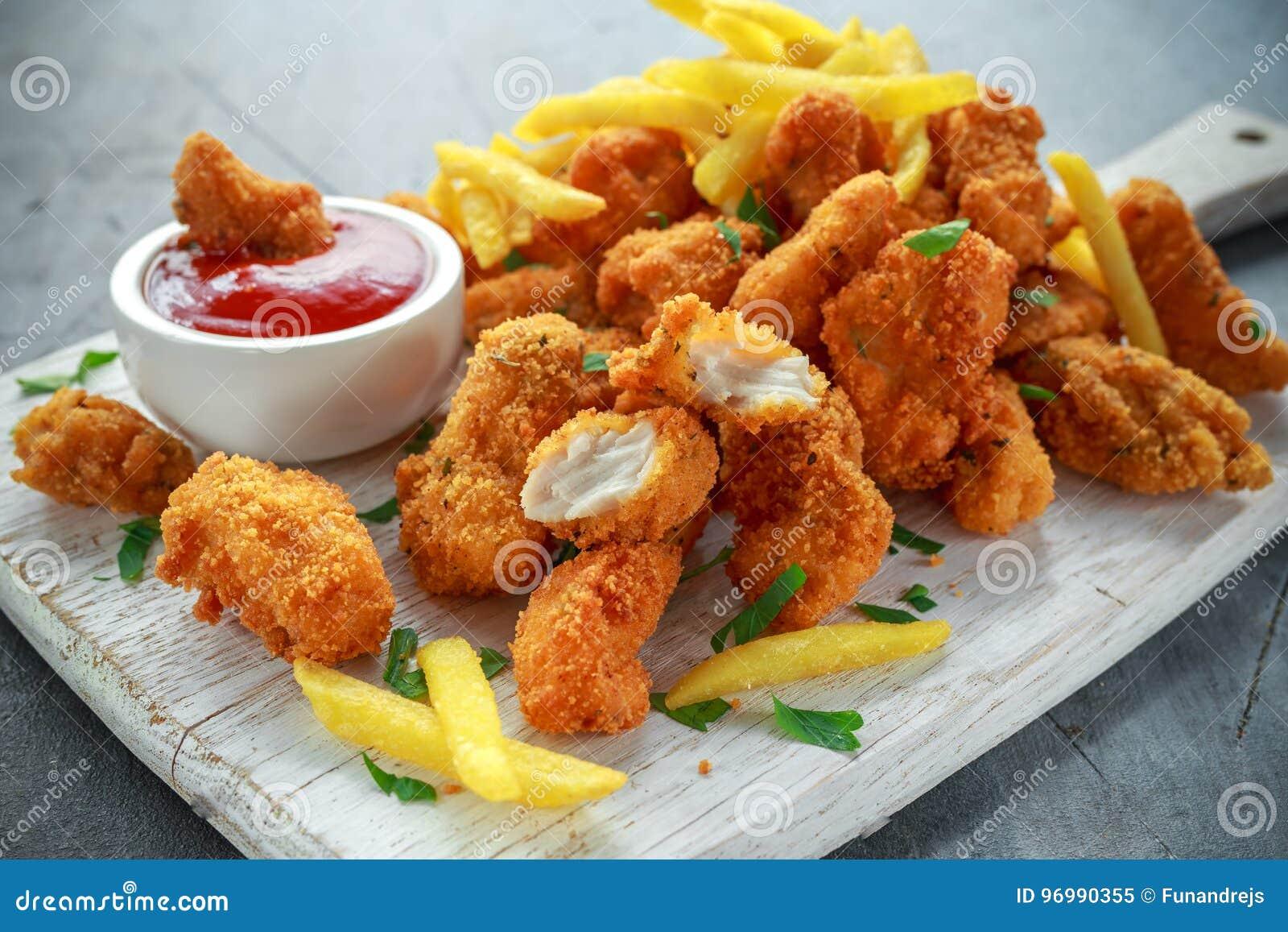 Smażyć crispy kurczak bryłki z francuza ketchupem na białej desce i dłoniakami
