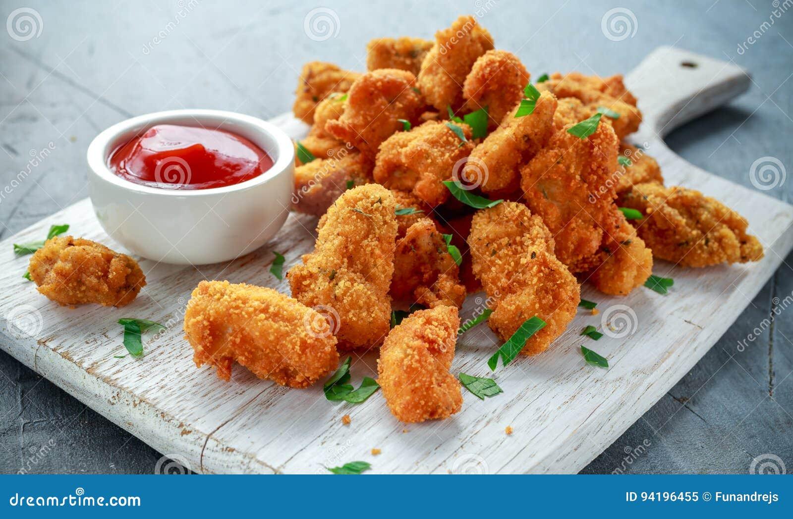 Smażyć crispy kurczak bryłki z ketchupem na białej desce