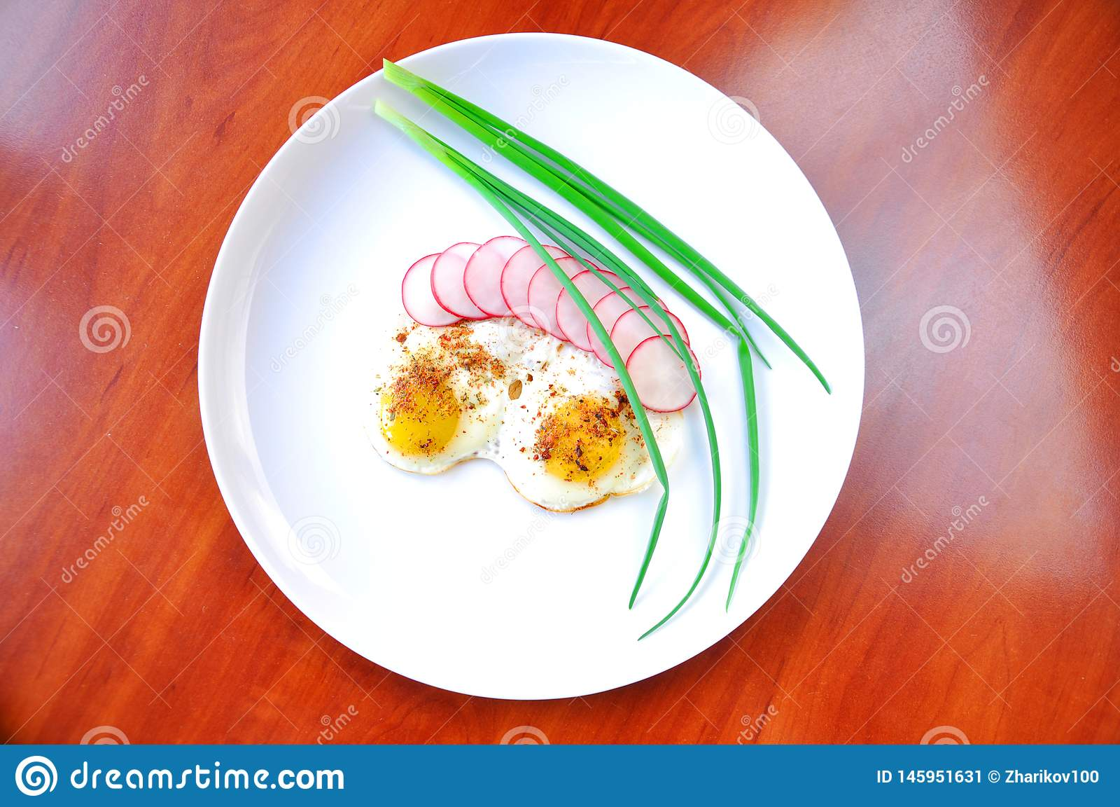 Smażyć rzodkwie w talerzu, jajka i cebule i