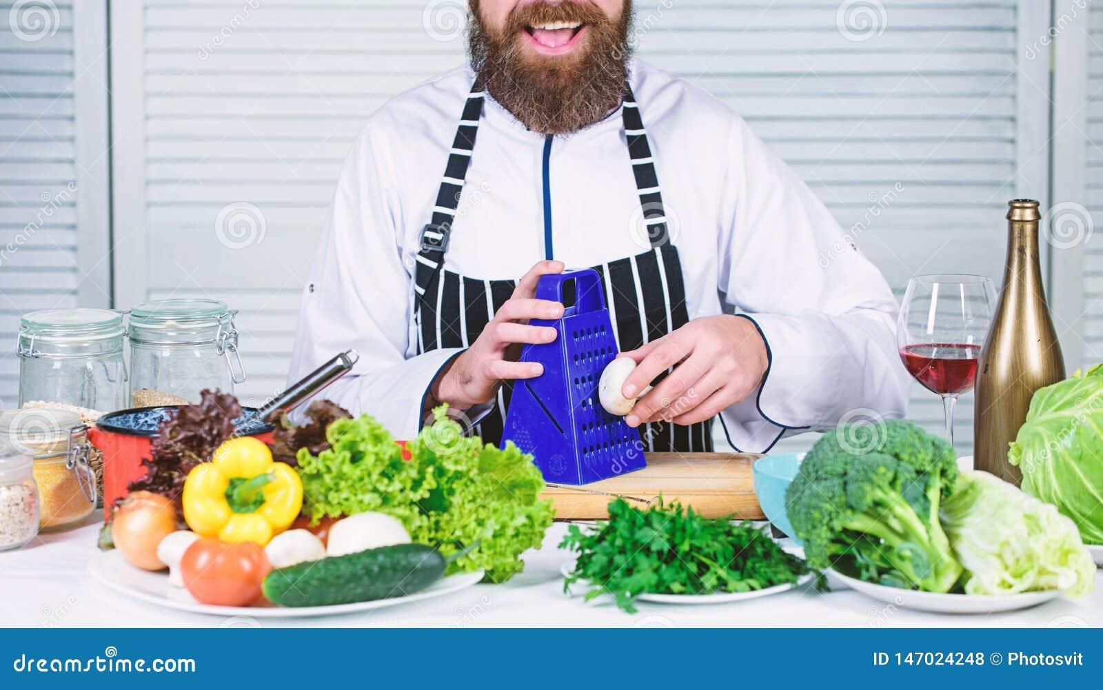 Smaak het Chef-kokmens in hoed Geheim smaakrecept vegetari?r Rijpe chef-kok met baard Gebaarde mensenkok in keuken