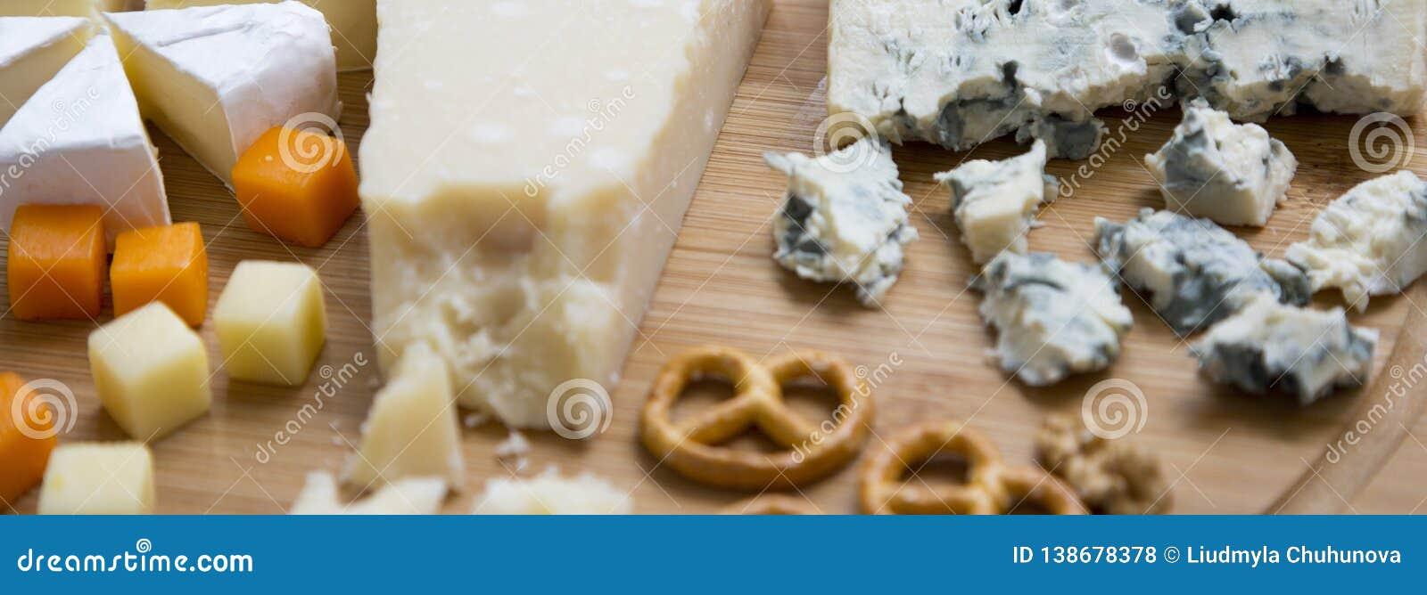 Smaka ostar: camembert, ädelost, brie, parmesan, mimolette och edam med kringlor och valnötter på runt bambubräde Mat