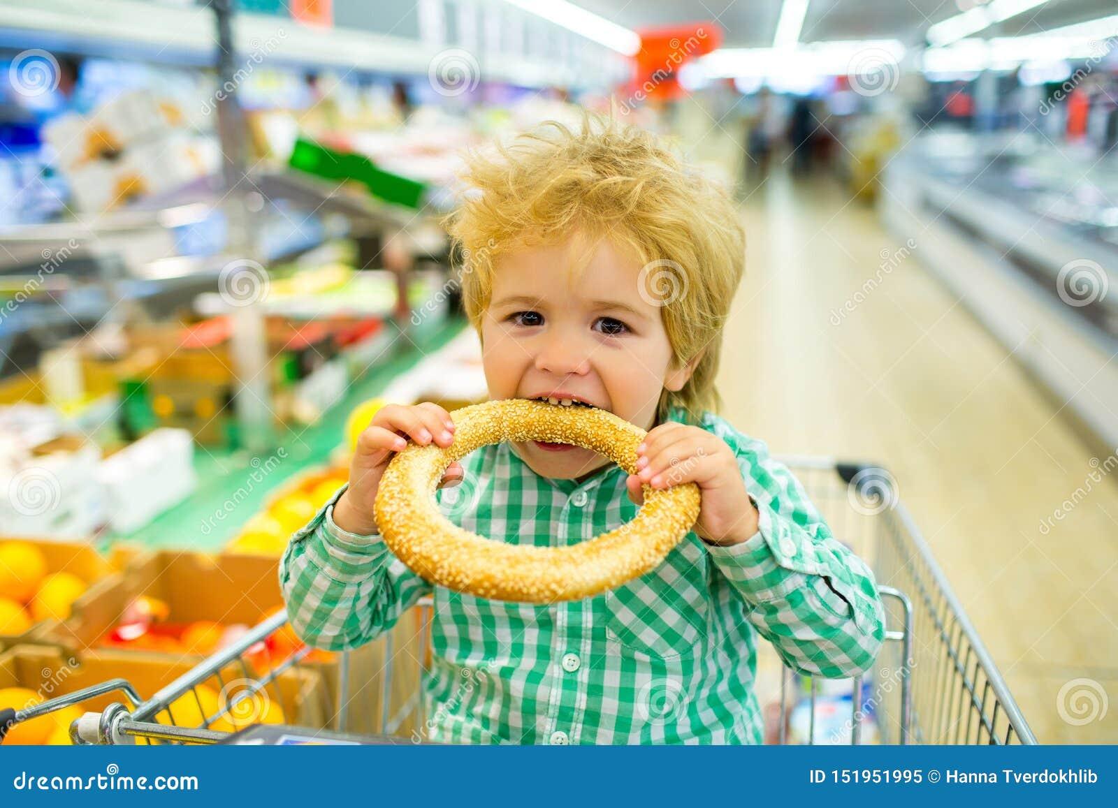 Smakelijk broodje Het ongezuurde broodje van jongensbeten met sesam in de supermarkt De producten van de bakkerij Het winkelen he