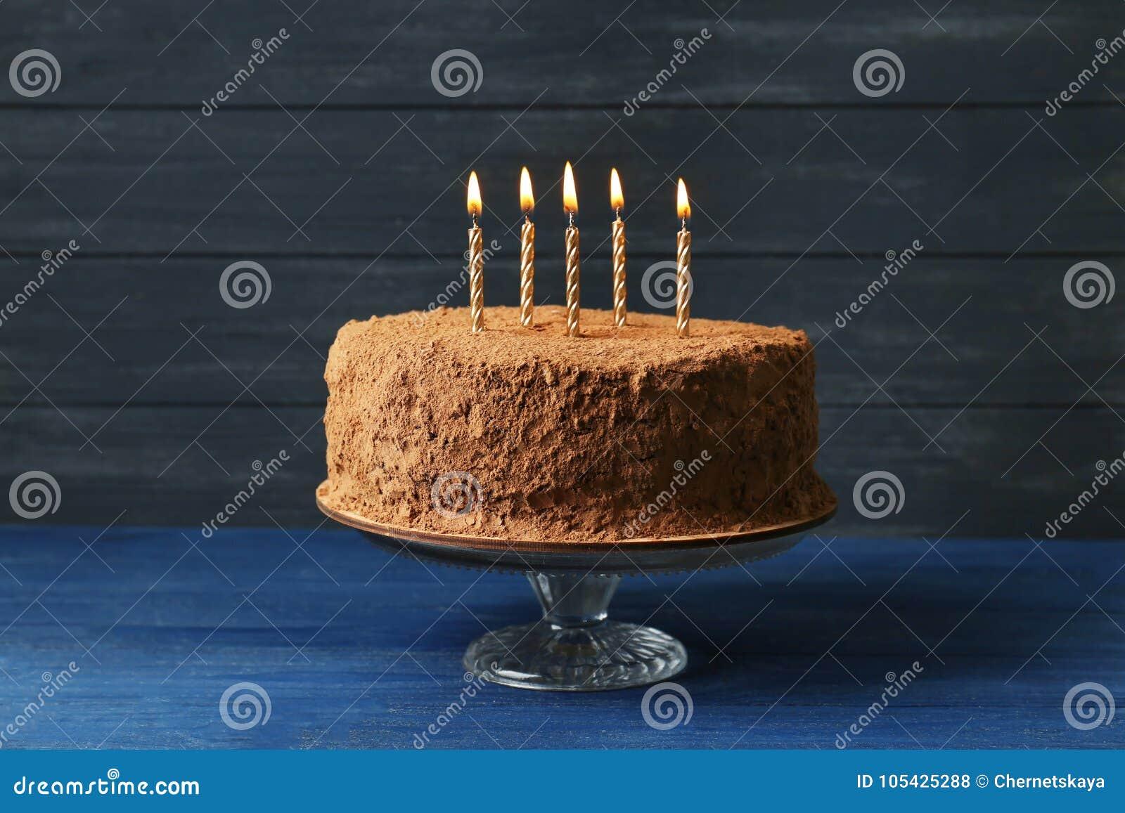 Smakelijke chocoladecake met kaarsen op houten muur