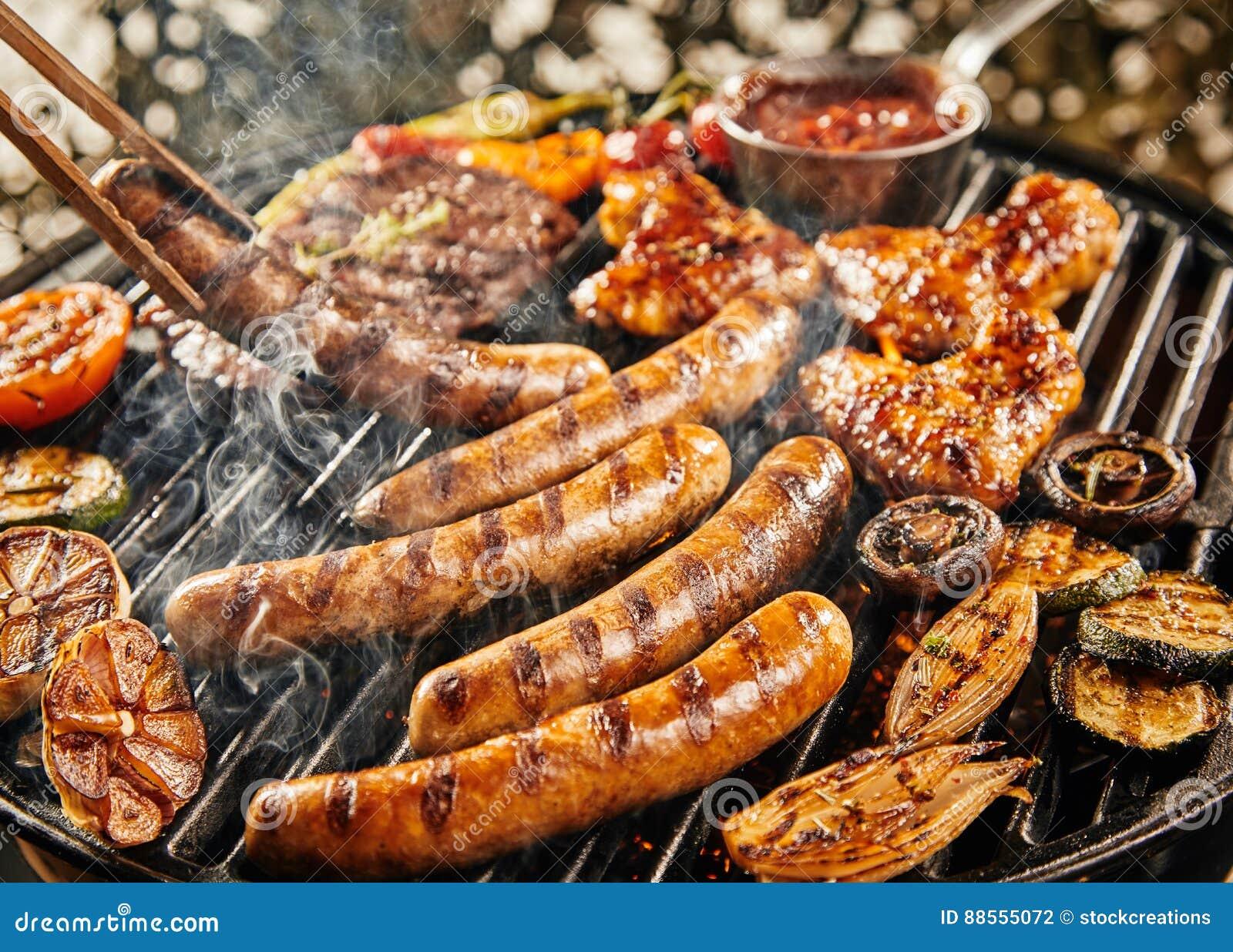 Smakelijke de zomerpicknick met het roosteren van voedsel op BBQ