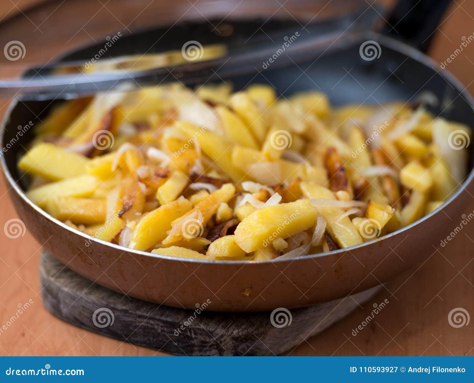 Smakelijke eigengemaakte gebraden die aardappels met uien in een pan worden gediend