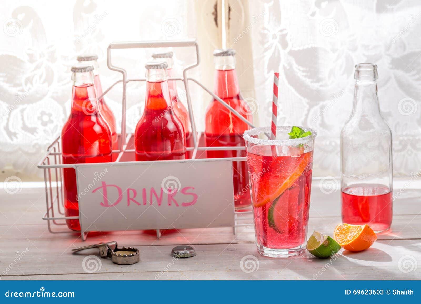 Smakelijke rode orangeade in fles met citrusvruchten