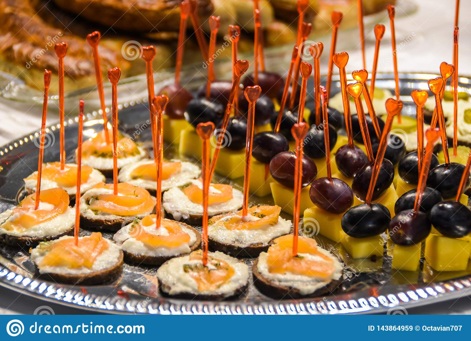 Smakelijke voorgerechten met kaas en vissen en druiven en kaas op zilveren schotel
