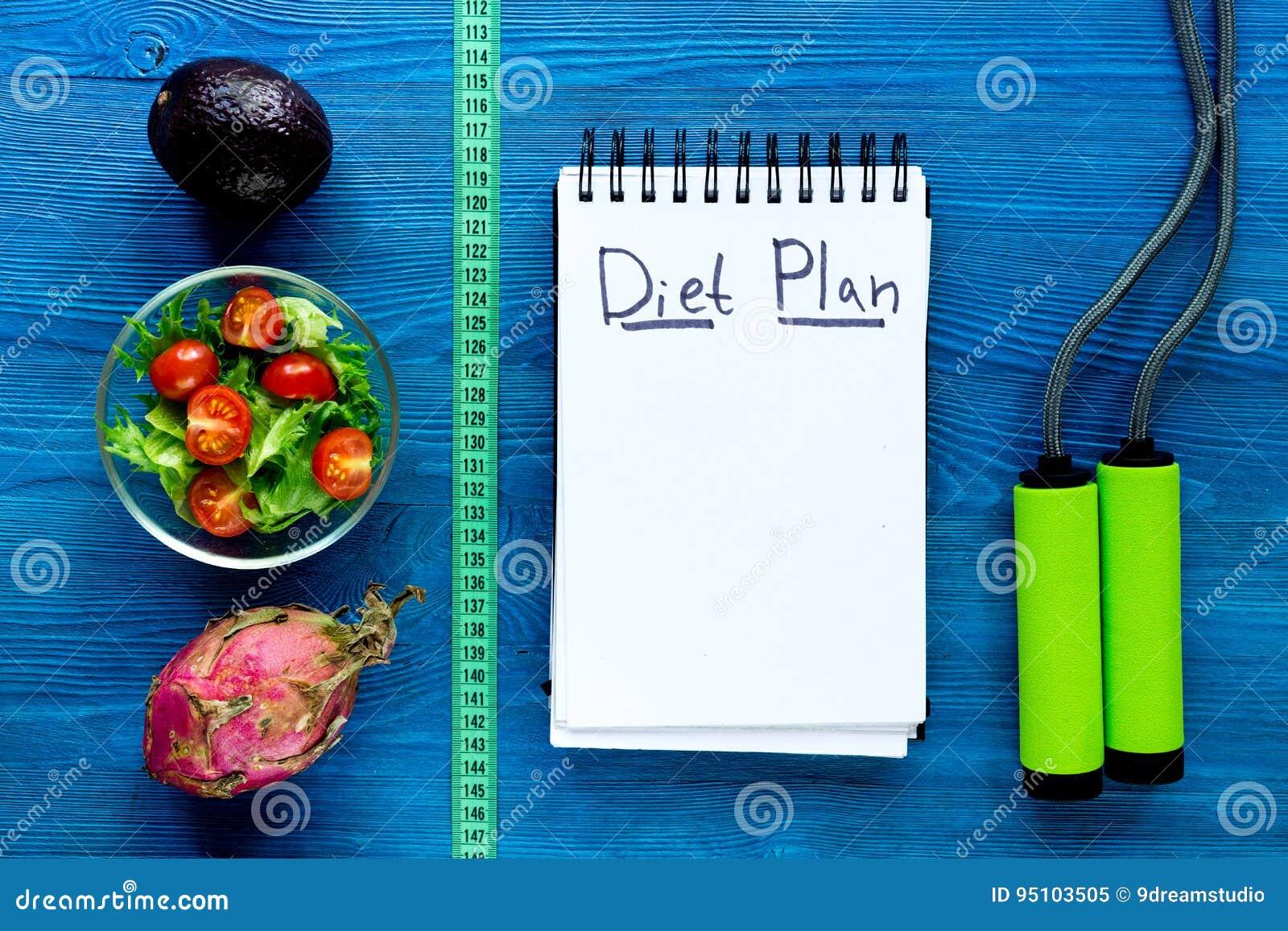 Smaklig mat för att banta Anteckningsboken för bantar planet, sallad, frukter och mätabandet på vit åtlöje för den bästa sikten f